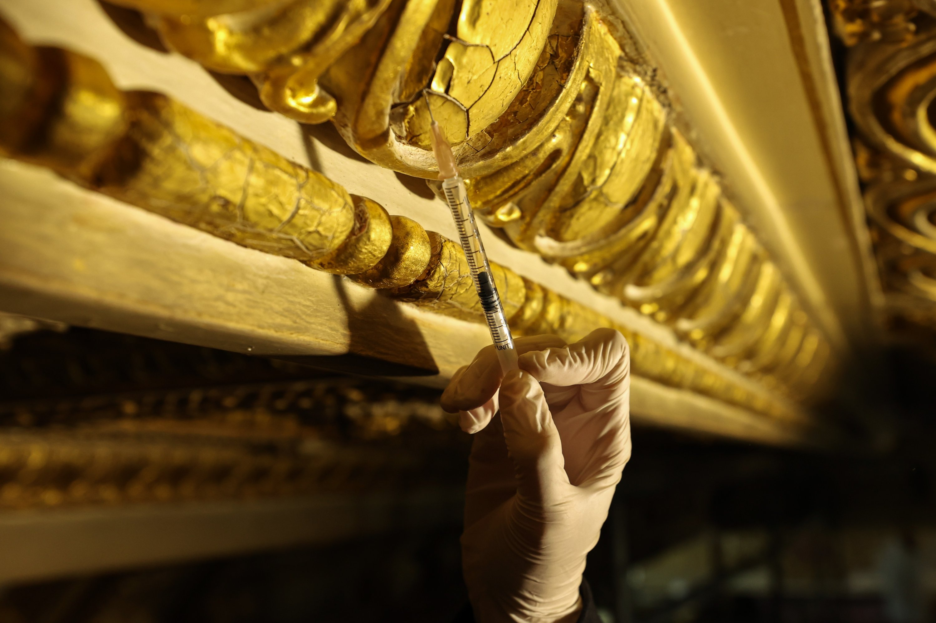 A close-up of a restorer's hand working on the decorations of the Süfera Hall, Dolmabahçe Palace, Istanbul, Turkey, April 17, 2021. (AA Photo)