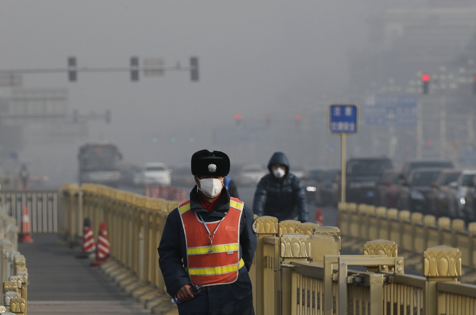 A traffic warden wearing a protection mask walks on a street near Tiananmen Square as the capital is blanketed by heavy smog, Beijing, China, Wednesday, Jan. 4, 2017. (AP Photo)