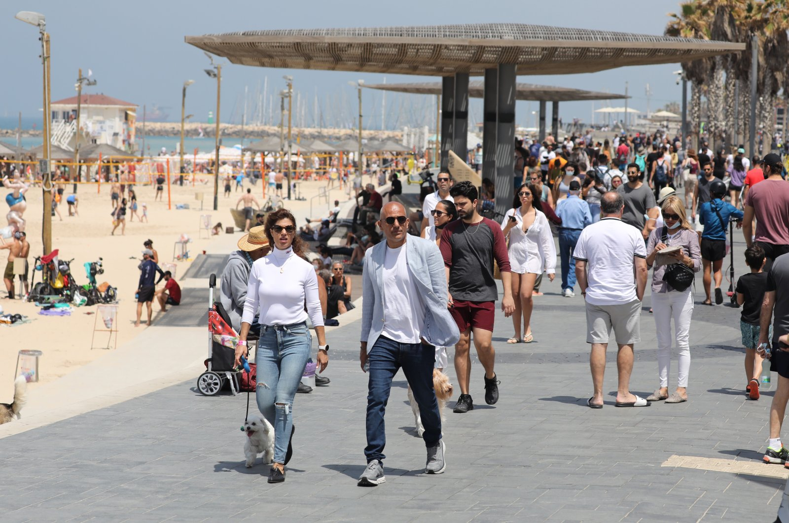 People without face masks enjoy a sunny day out at a beach in Tel Aviv, Israel, April 17, 2021. (EPA Photo)