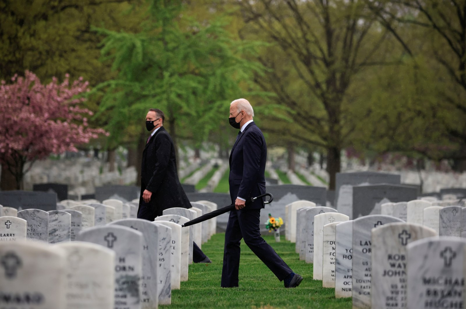 U.S. President Joe Biden carries an umbrella as he walks among graves in a visit to pay his respects to fallen veterans of the Afghan conflict, in Arlington National Cemetery in Arlington, Virginia, U.S., April 14, 2021. (Reuters Photo)
