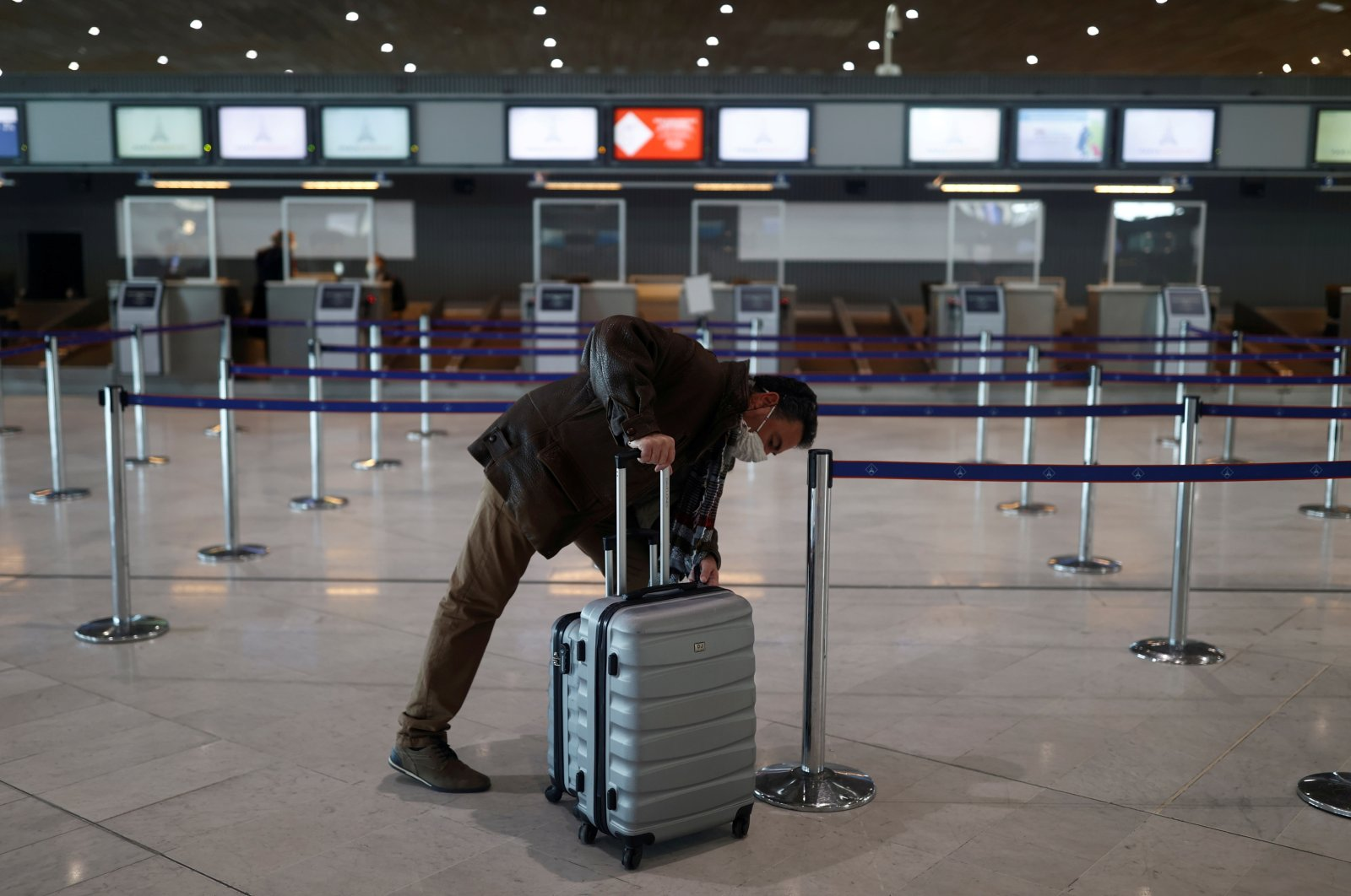 A passenger waits for check-in in the departures area of Terminal 2E at Charles-de-Gaulle airport amid the coronavirus outbreak, in Roissy, near Paris, France, April 2, 2021. (Reuters Photo)