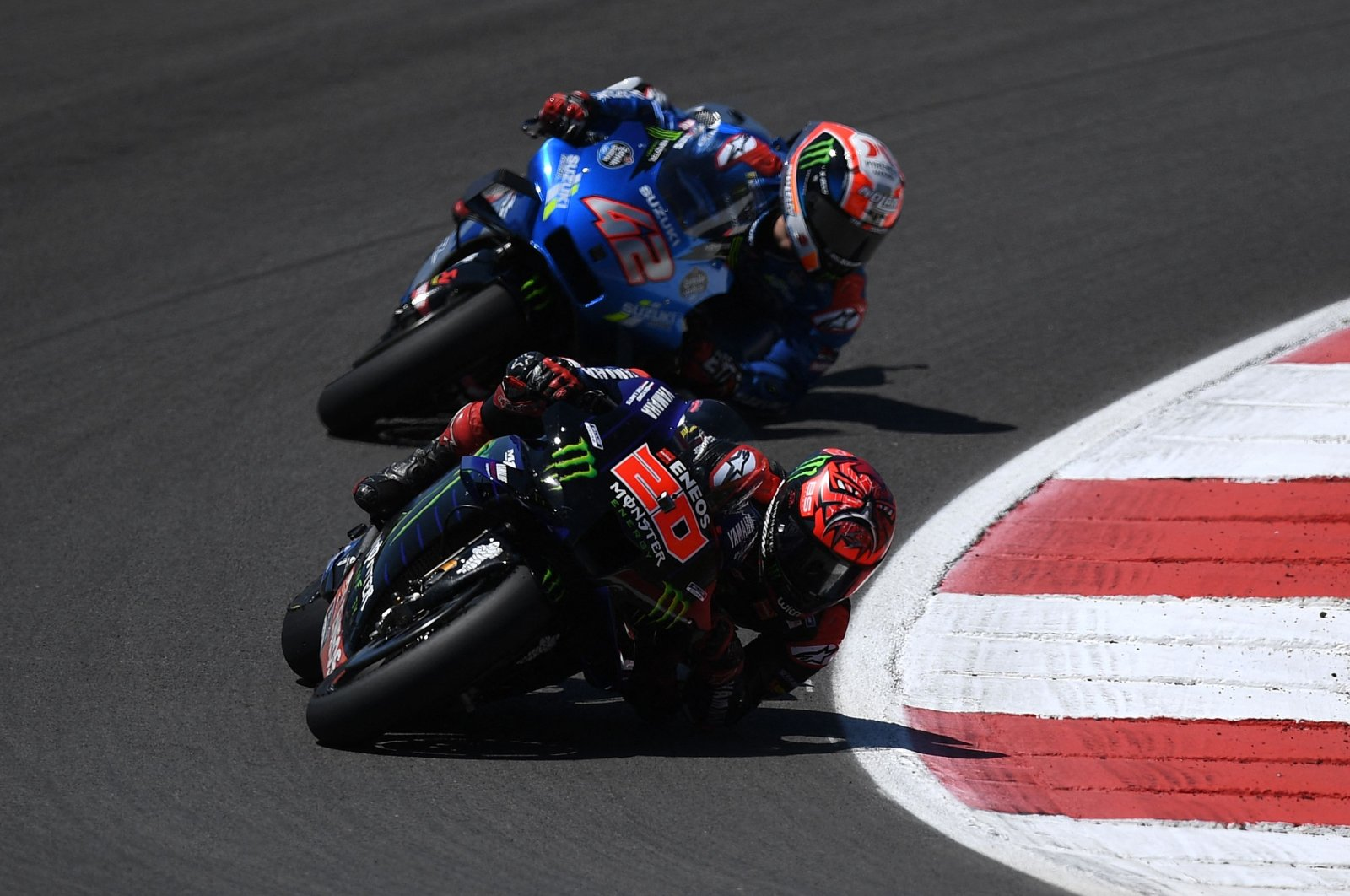 Monster Energy Yamaha MotoGP's French rider Fabio Quartararo and Team Suzuki Ecstar's Spanish rider Alex Rins (back) compete in the MotoGP Portuguese Grand Prix at the Algarve International Circuit, Portimao, Portugal, April 18, 2021. (AFP Photo)