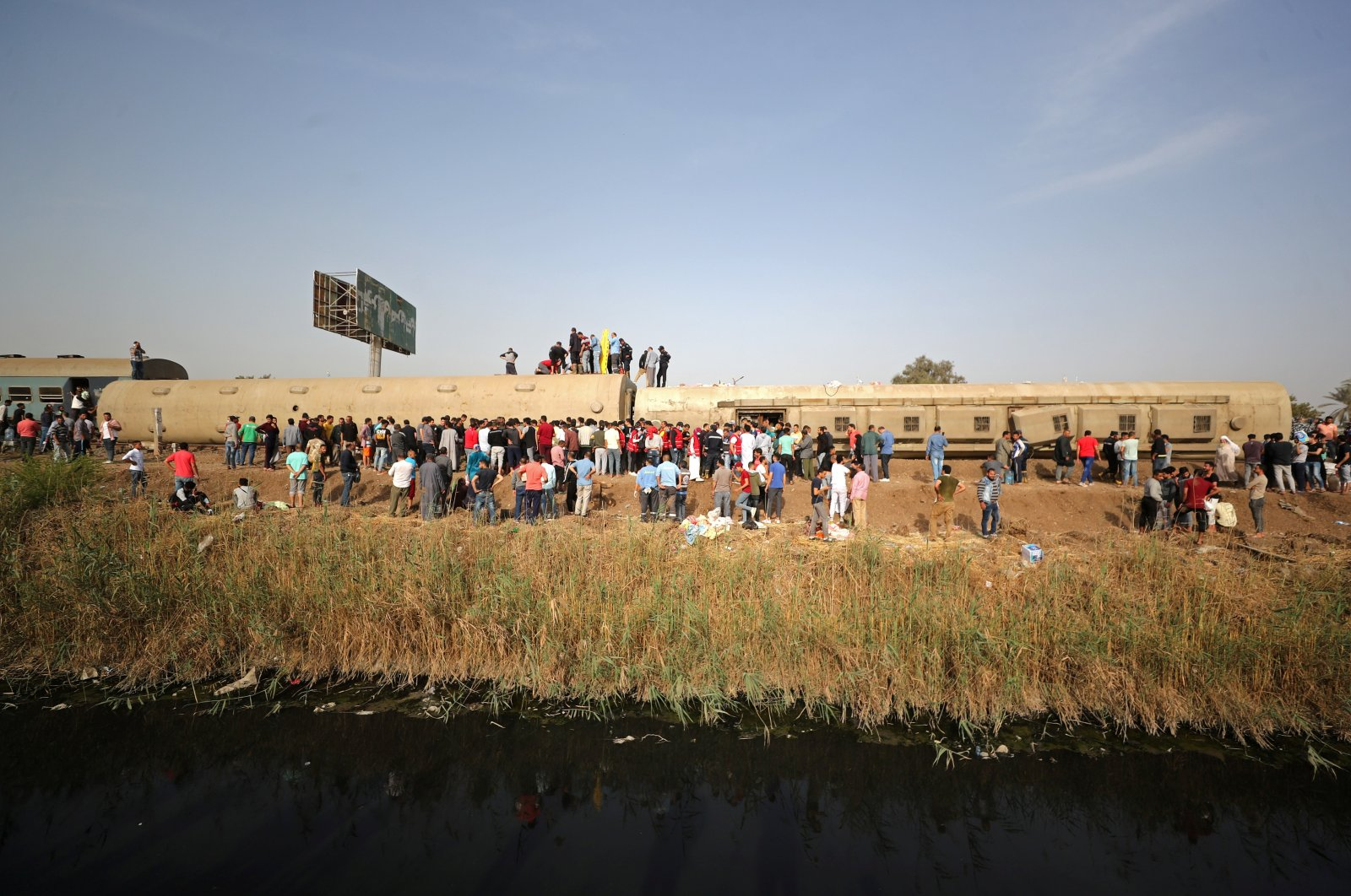People gather at the site where train carriages derailed in Qalyubia province, north of Cairo, Egypt, April 18, 2021. (Reuters Photo)