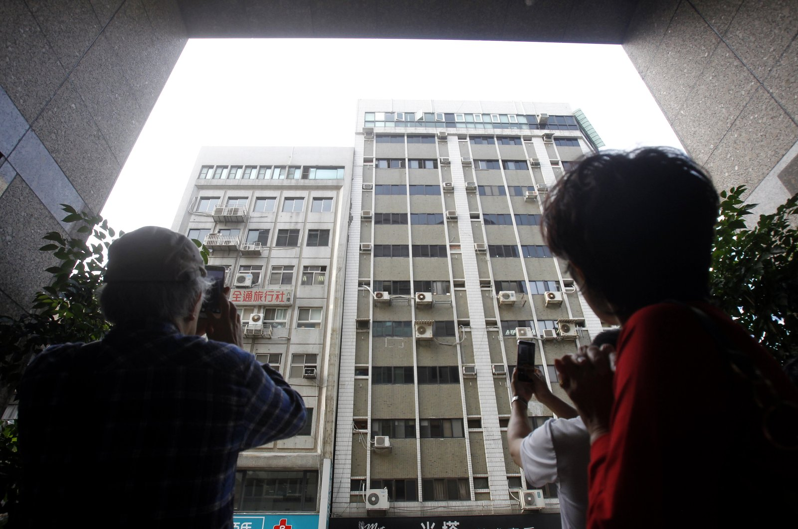 People take photos of buildings damaged by an earthquake in Taipei, Taiwan, Thursday, April 18, 2019. (AP File Photo)