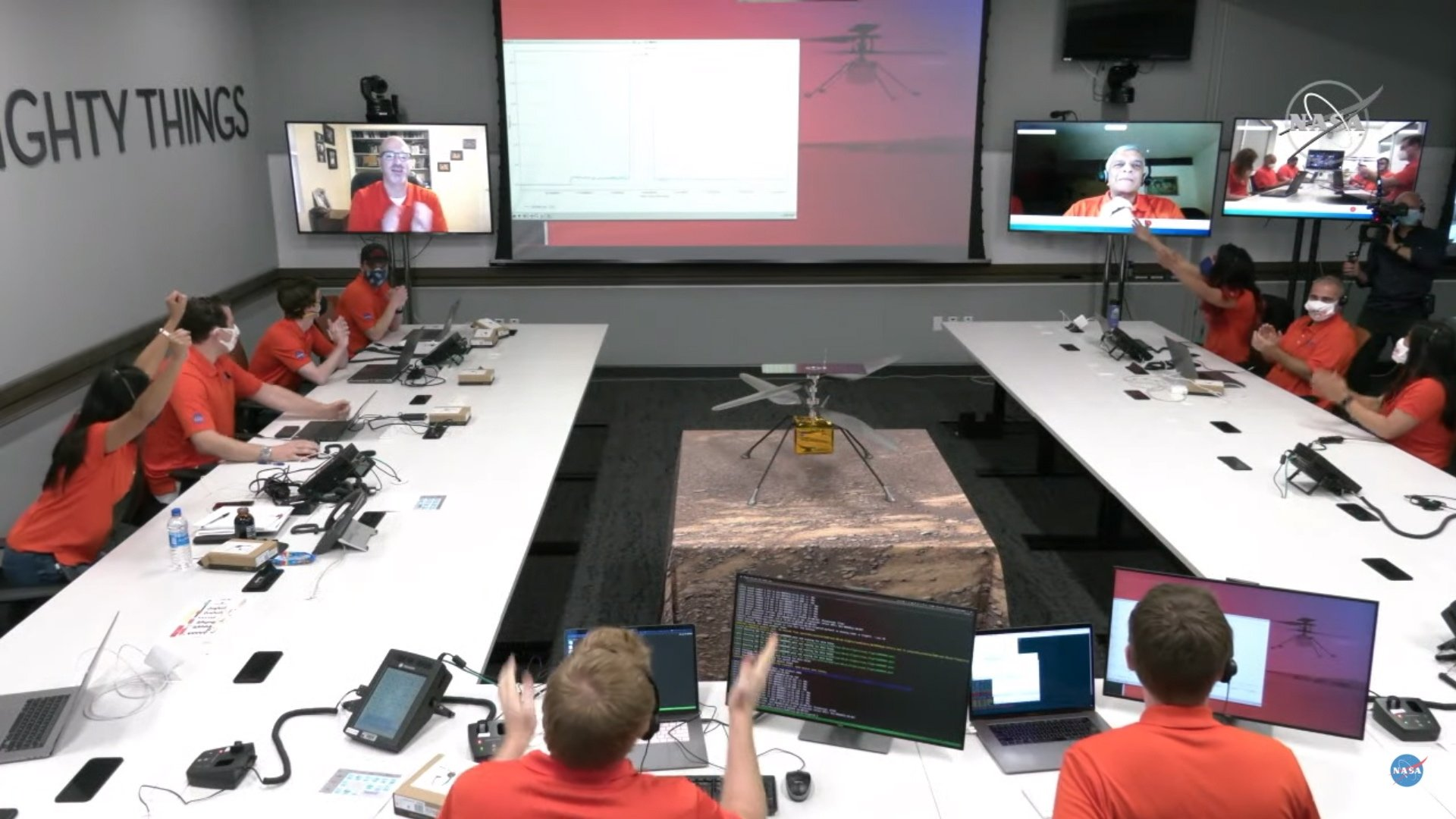 A handout video still taken from a livestream by NASA shows engineers celebrating after data downlinked from NASA's Ingenuity Helicopter suggested a successful first test flight on Mars, at the control room at NASA's Jet Propulsion Laboratory in Pasadena, California, U.S., April 19, 2021. (EPA/NASA handout)