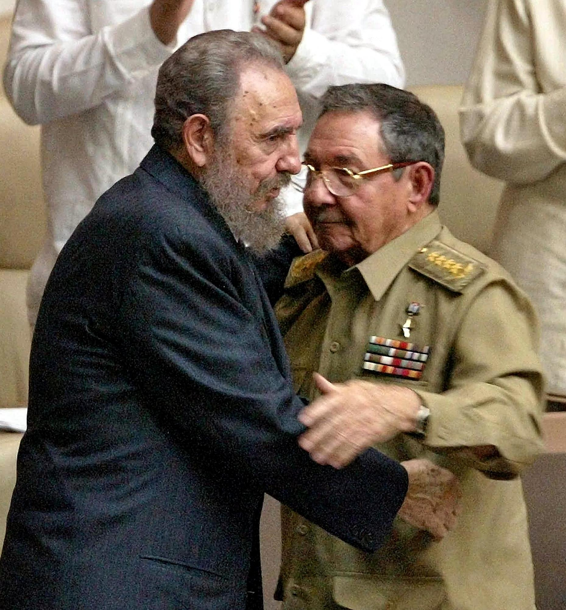 Cuban President Fidel Castro (L), the newly elected president of the Cuban State Council and of the Cuban Council of Ministers, is congratulated by his brother, Vice-President and Minister of the Armed Forces General Raul Castro, in Havana, Cuba, March 5, 2003. (AFP Photo)