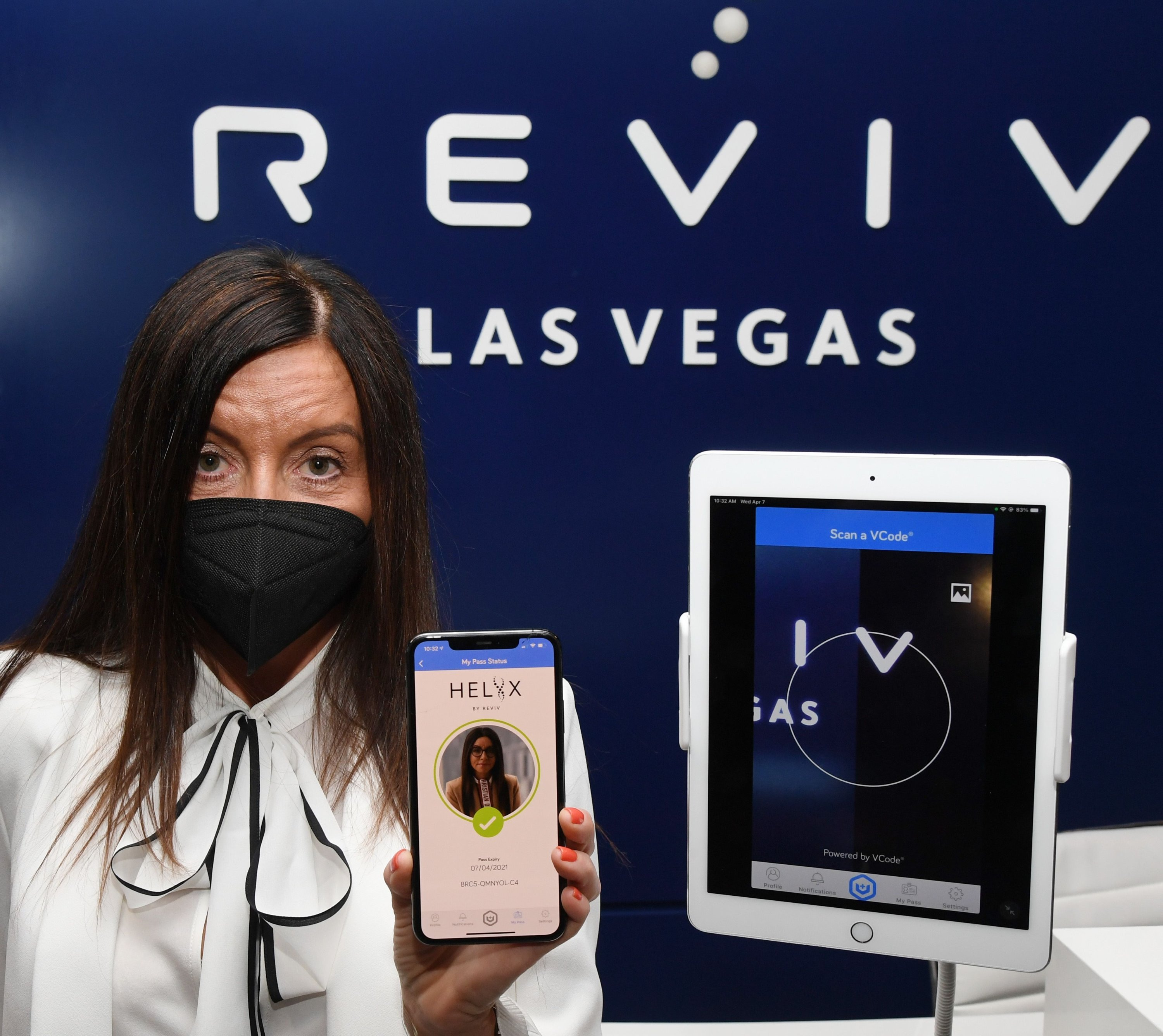 REVIV Global President and CEO Sarah Lomas uses a cell phone and an iPad to demonstrate the HELIIX Health Passport at REVIV at The Cosmopolitan of Las Vegas in Las Vegas, Nevada, April 7, 2021. (Getty Images/AFP)
