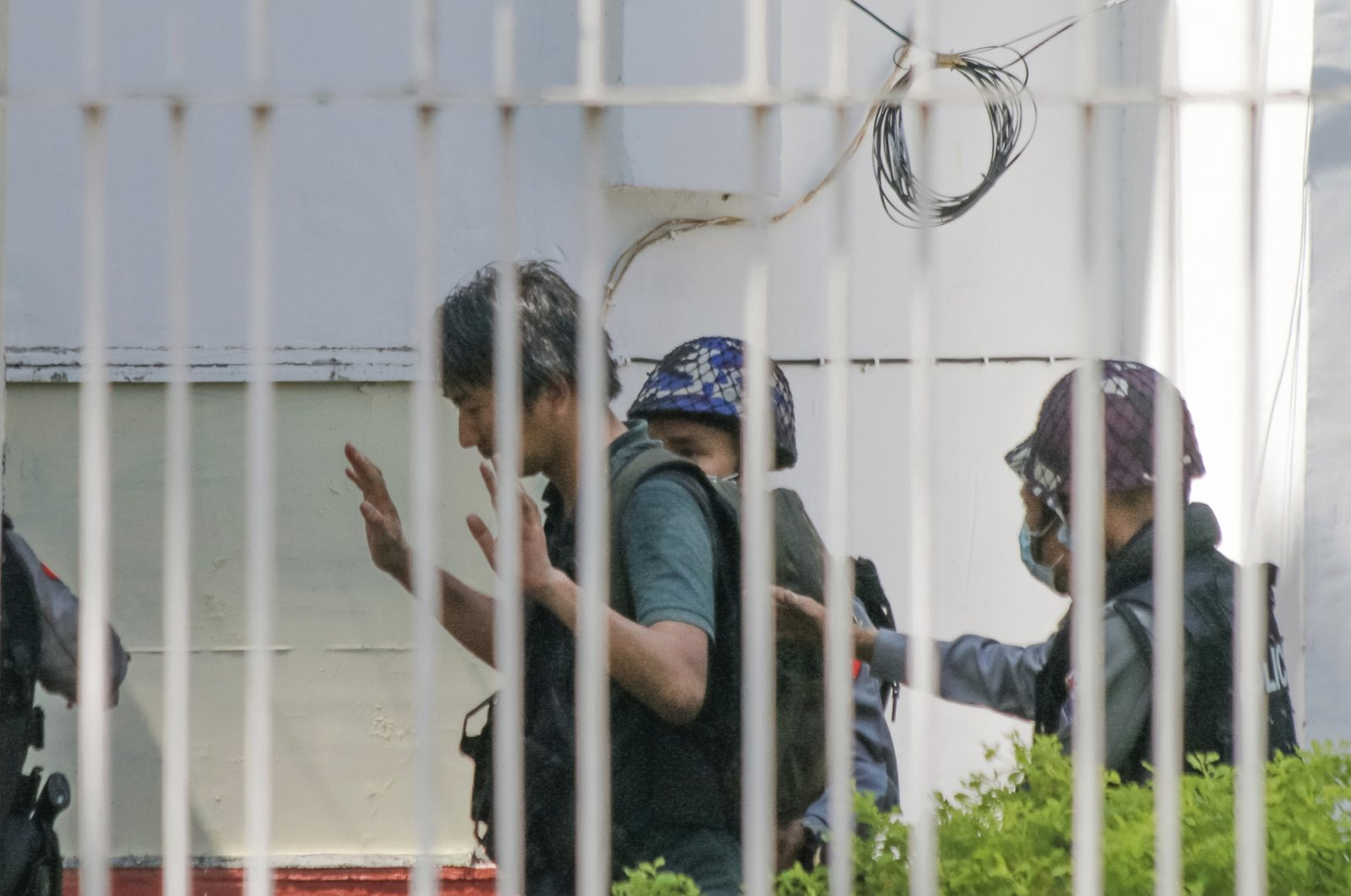 Japanese journalist Yuki Kitazumi raises his hands as he is escorted by police upon arrival at the Myaynigone police station in Sanchaung township in Yangon, Myanmar, Feb. 26, 2021. (AP Photo)