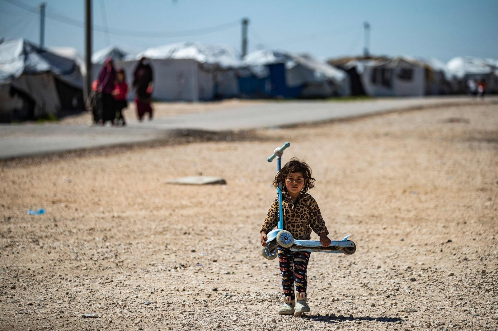 A child carries a kick scooter along a thin tarmac road beyond rows of white tents at Camp Roj, where relatives of people suspected of belonging to Daesh are held, in the countryside near al-Malikiyah (Derik) in Syria's northeastern Hasakah province, March 28, 2021.  (AFP)
