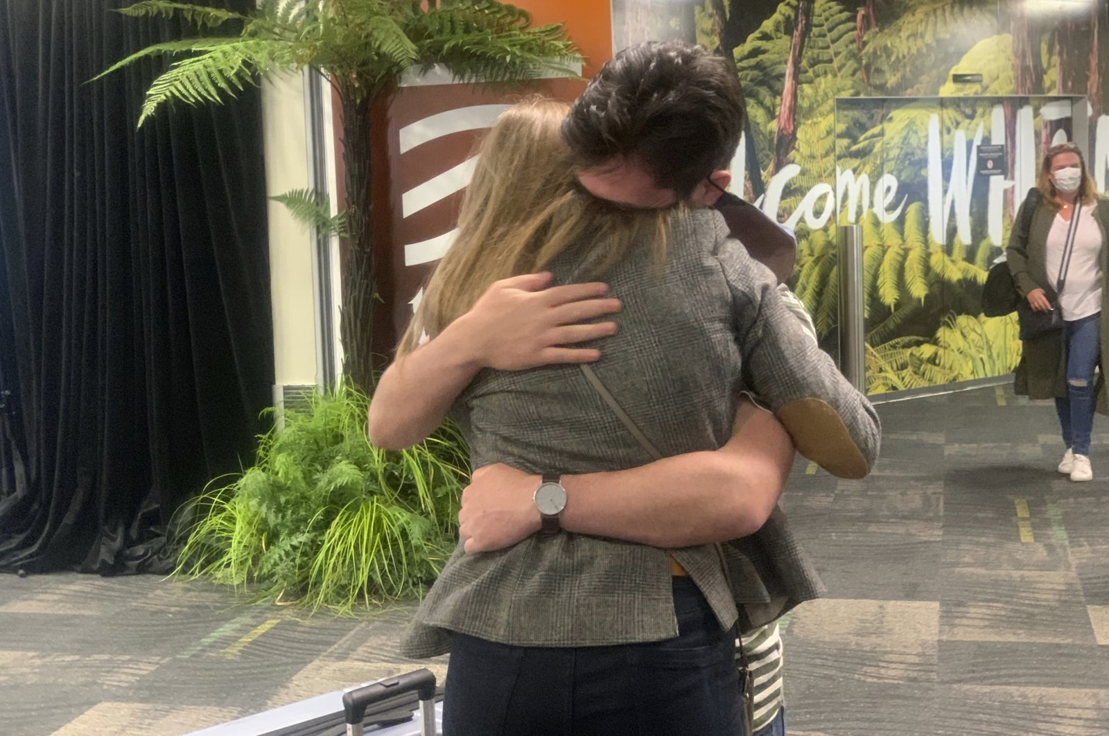 A passenger arriving from Sydney at Wellington International Airport hugs a loved one in Wellington, New Zealand, April 19, 2021. (AP Photo)