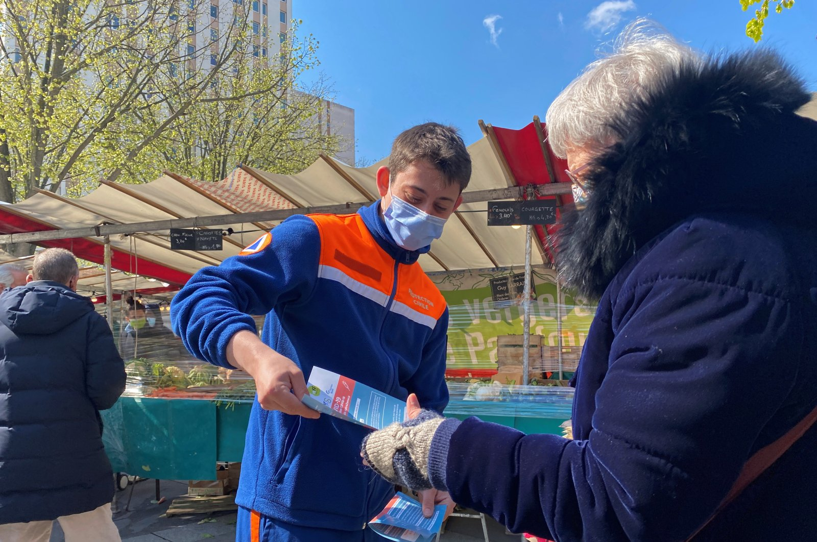 """Volunteers from the French """"Protection Civile"""" association hand out leaflets at a fresh producer market to try to persuade Parisians over 55 to take the AstraZeneca vaccine, amid the coronavirus disease (COVID-19) pandemic, Paris, France, April 16, 2021. (Reuters Photo)"""
