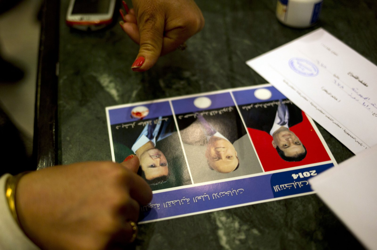 A woman votes for Bashar Assad by marking the ballot with blood from her pricked finger, in Damascus, Syria, June 3, 2014. (AP Photo)