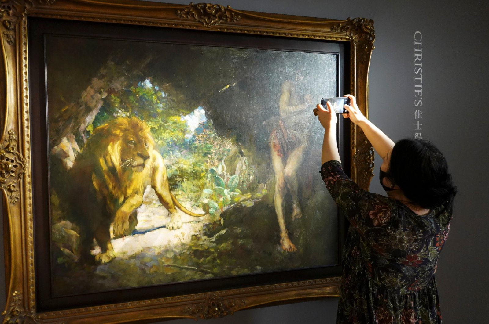 "A journalist takes pictures of the 1924 painting by Xu Beihong titled ""Slave and Lion"" during a media event before the item is auctioned at Christie's, in Hong Kong, China, April 19, 2021. (REUTERS Photo)"