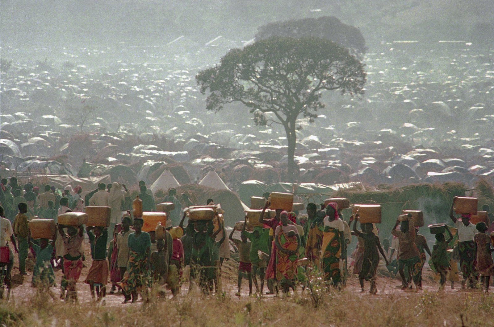Refugees who fled the ethnic bloodbath in neighboring Rwanda carry water containers back to their huts at the Benaco refugee camp in Tanzania, near the border with Rwanda, May 17, 1994. (AP Photo)