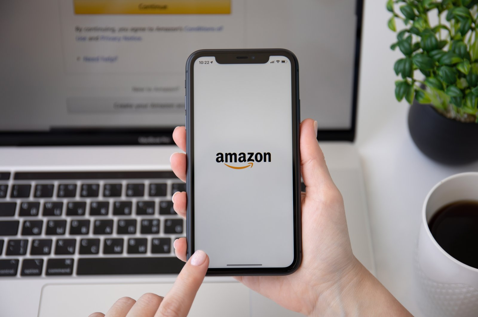A woman holds a smartphone with the logo of online shopping service Amazon on the screen, Alanya, Turkey, June 7, 2020. (Shutterstock Photo)