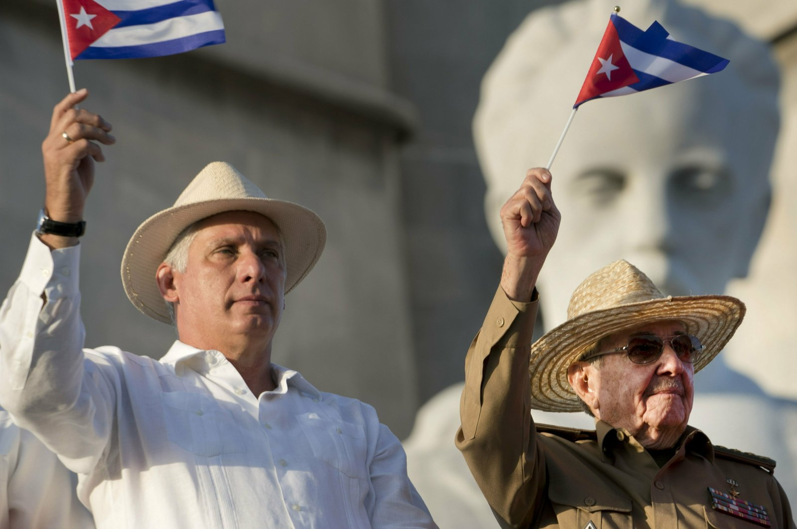Cuba's President Miguel Diaz-Canel (L) and former Cuban President Raul Castro wave Cuban flags as they watch the annual May Day parade file past at Revolution Square in Havana, Cuba, May 1, 2019. (AP Photo)
