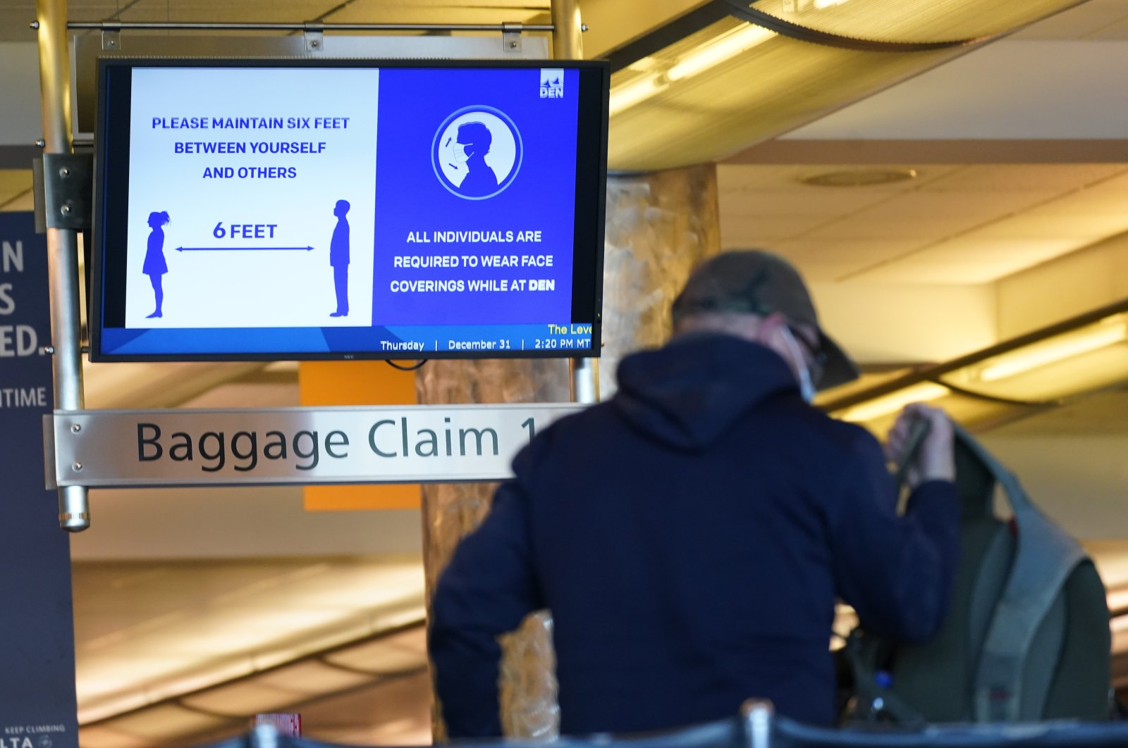 An electronic sign advises travelers to wear face masks and practice social distancing while passing through the main terminal of Denver International Airport in Denver, Colorado, the U.S., Dec. 31, 2020. (AP Photo)