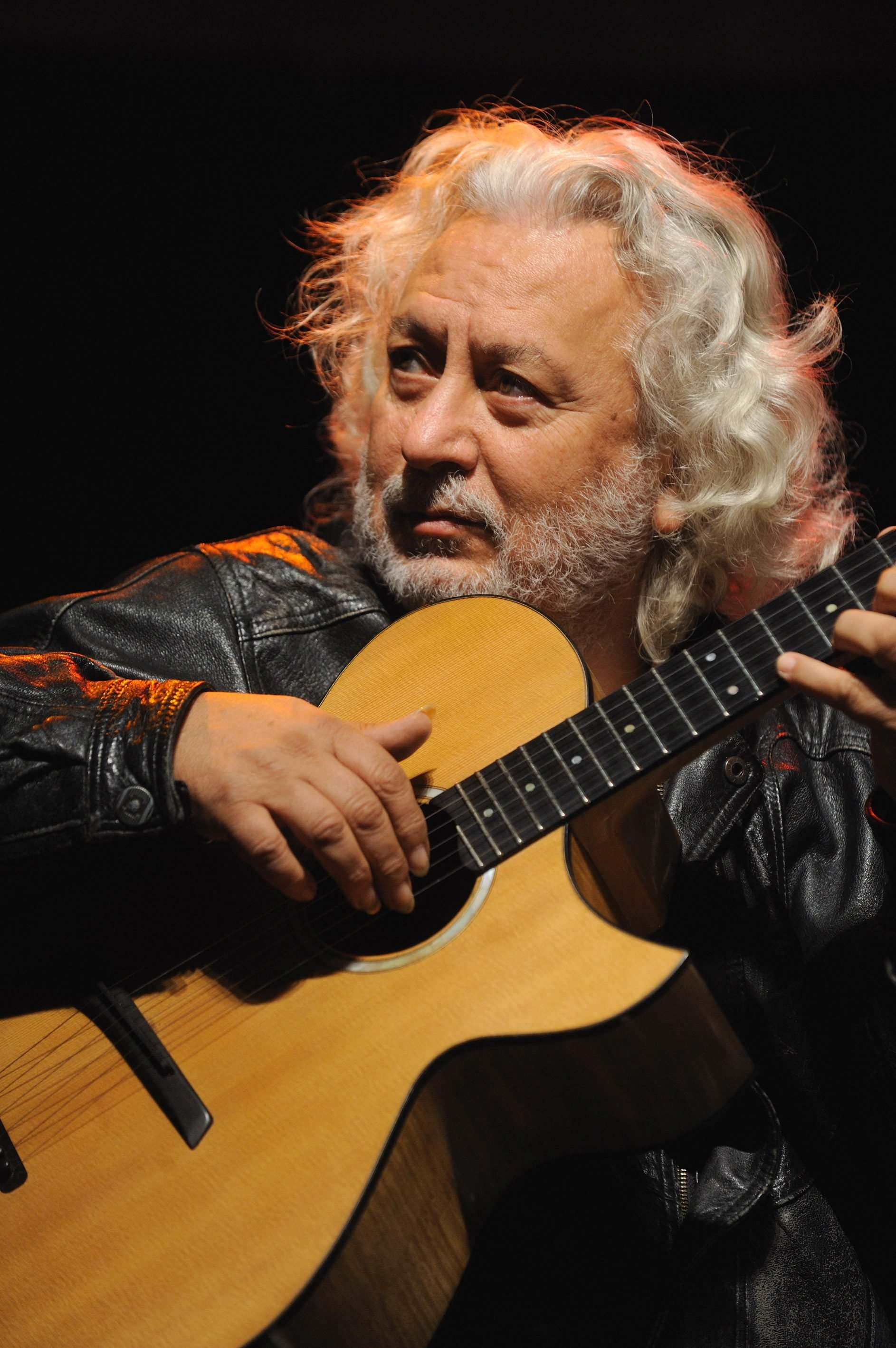 Erkan Oğur holding his guitar during a concert. (AA Photo)