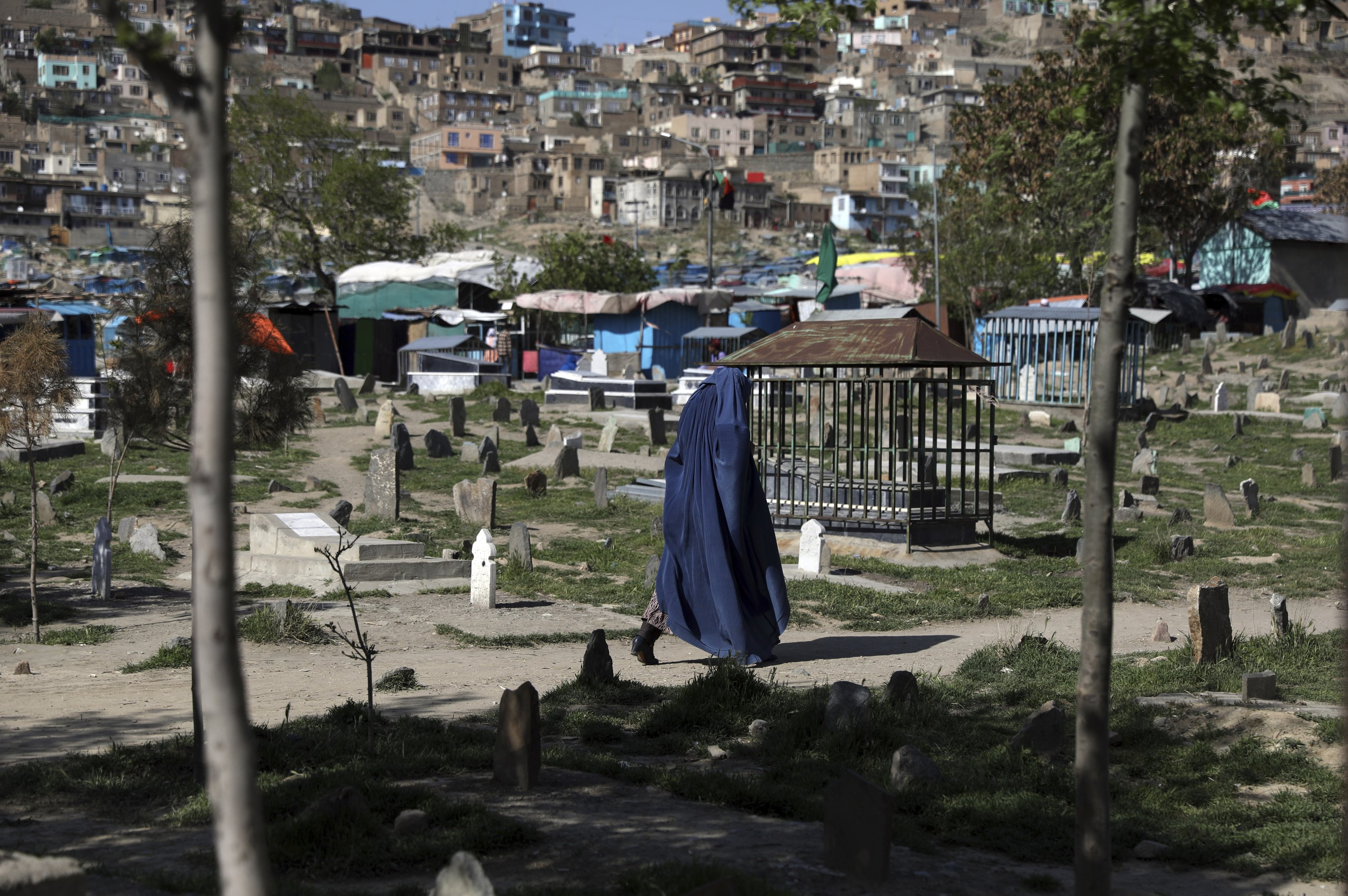 A burqa-clad woman walks in a cemetery during the holy fasting month of Ramadan in Kabul, Afghanistan, April 18, 2021. (AP Photo)