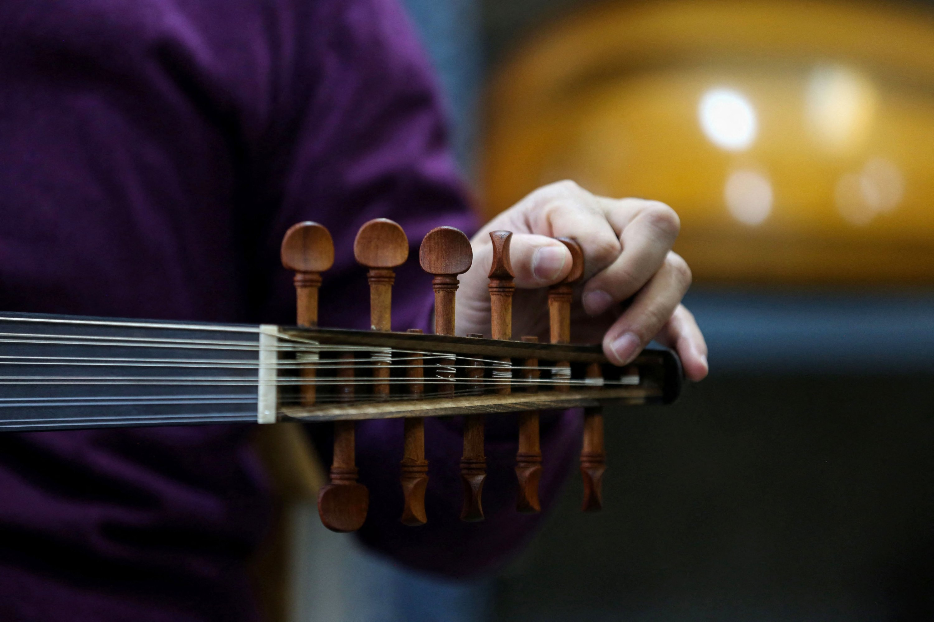 Iranian master player and instructor Hamid Khansari tests a new instrument at luthier Fatemeh Moussavi's (unseen) oud-making workshop in the capital Tehran, Iran, Dec. 14, 2020. (AFP Photo)