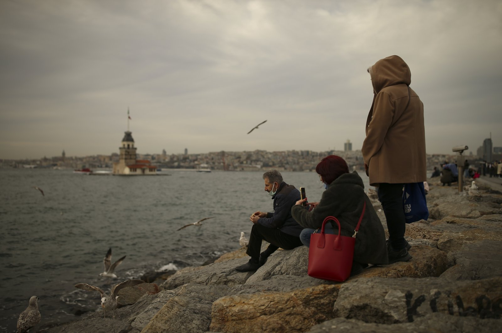 Overlooking Istanbul's Maiden's Tower, people sit by the shore of the Bosporus which separates the metropolis between European and Asian sides, Turkey, Feb. 11, 2021. (AP Photo)