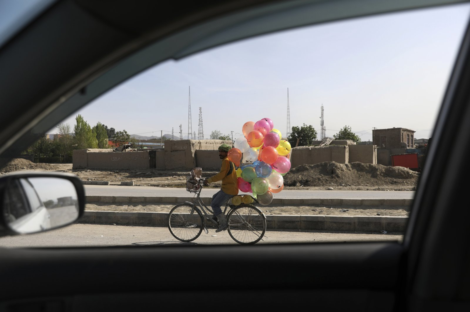 An Afghan balloon vendor riding his bicycle looks for customers in Kabul, Afghanistan, April 20, 2021. (AP Photo)