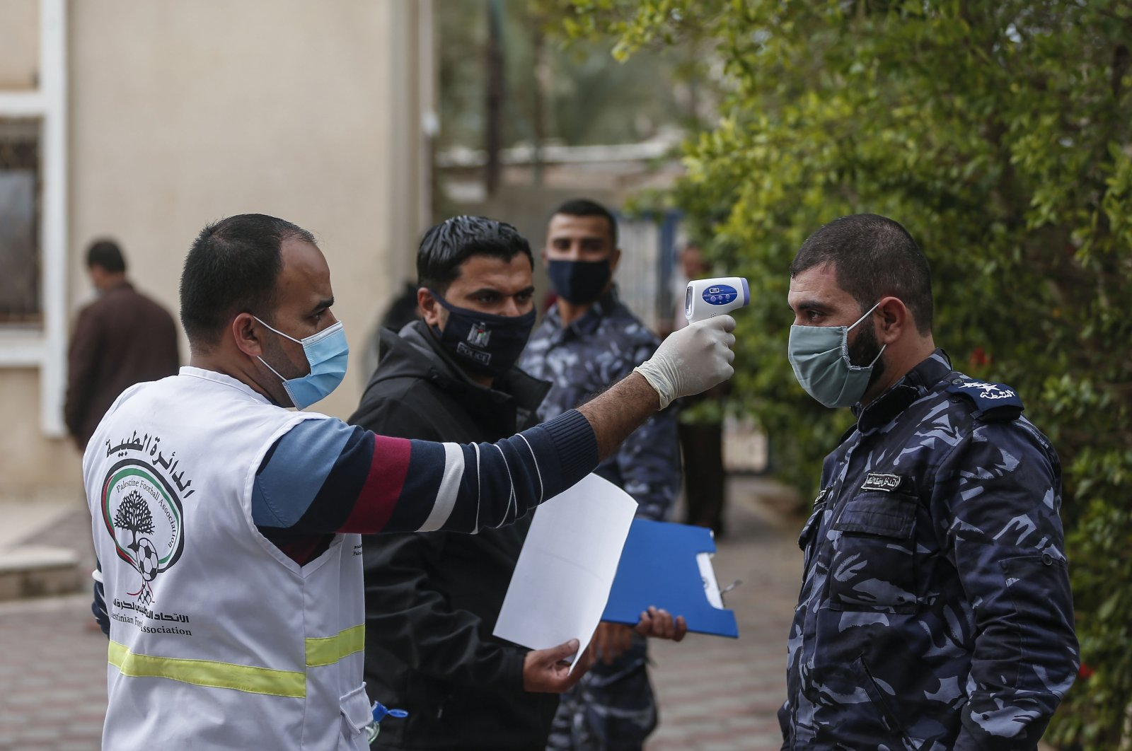 A Palestinian medical worker checks the temperature of a member of the security staff ahead of the final Gaza Cup match between Shabab Rafah and Khadamat Rafah football clubs, at the Mohammed al-Dura Stadium in Deir al-Balah in central Gaza Strip, Nov. 15, 2020. (AFP Photo)