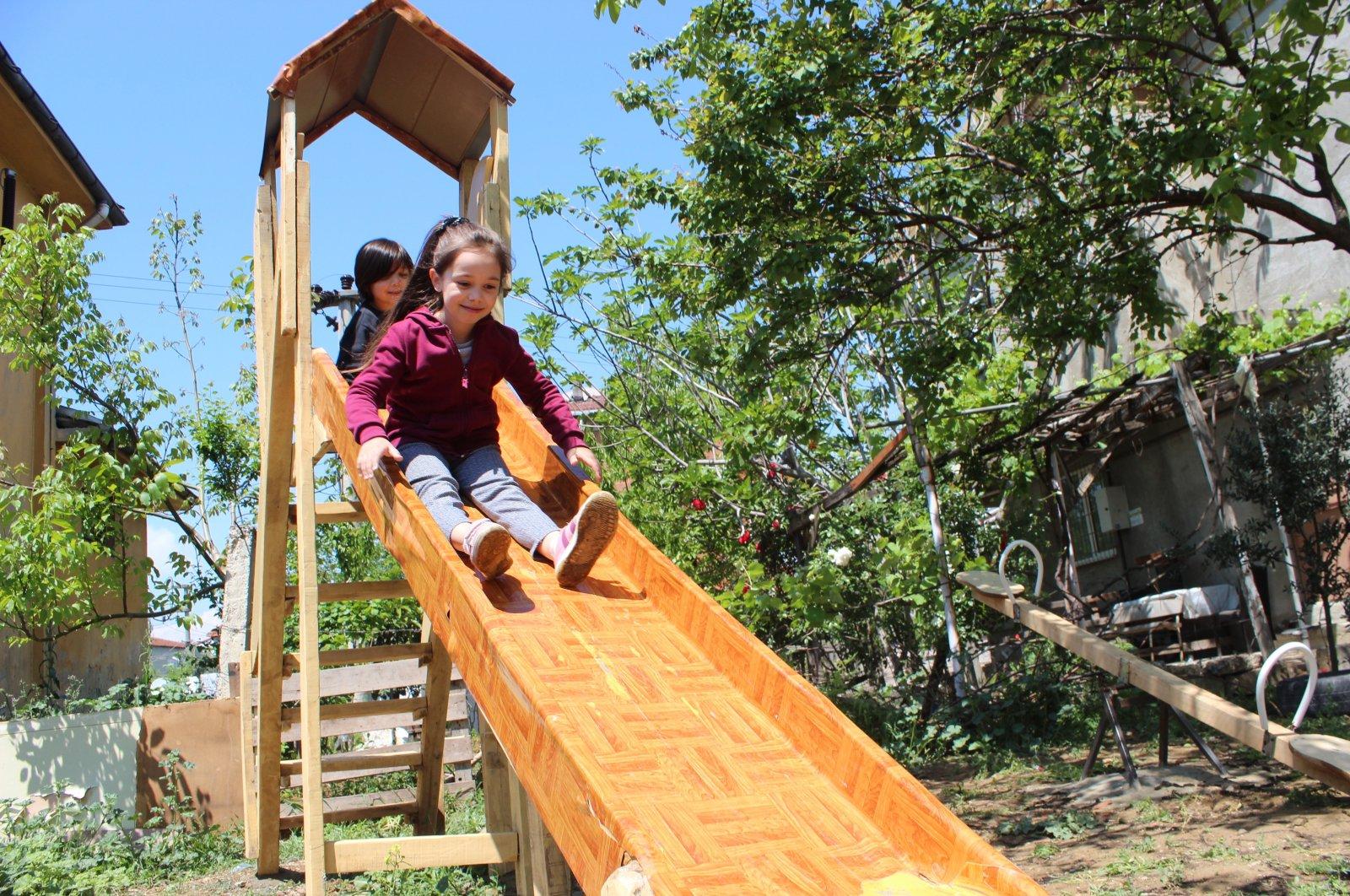 Children slide down a slide in the backyard of their house, in Kocaeli, northwestern Turkey, May 11, 2020. (İHA PHOTO)
