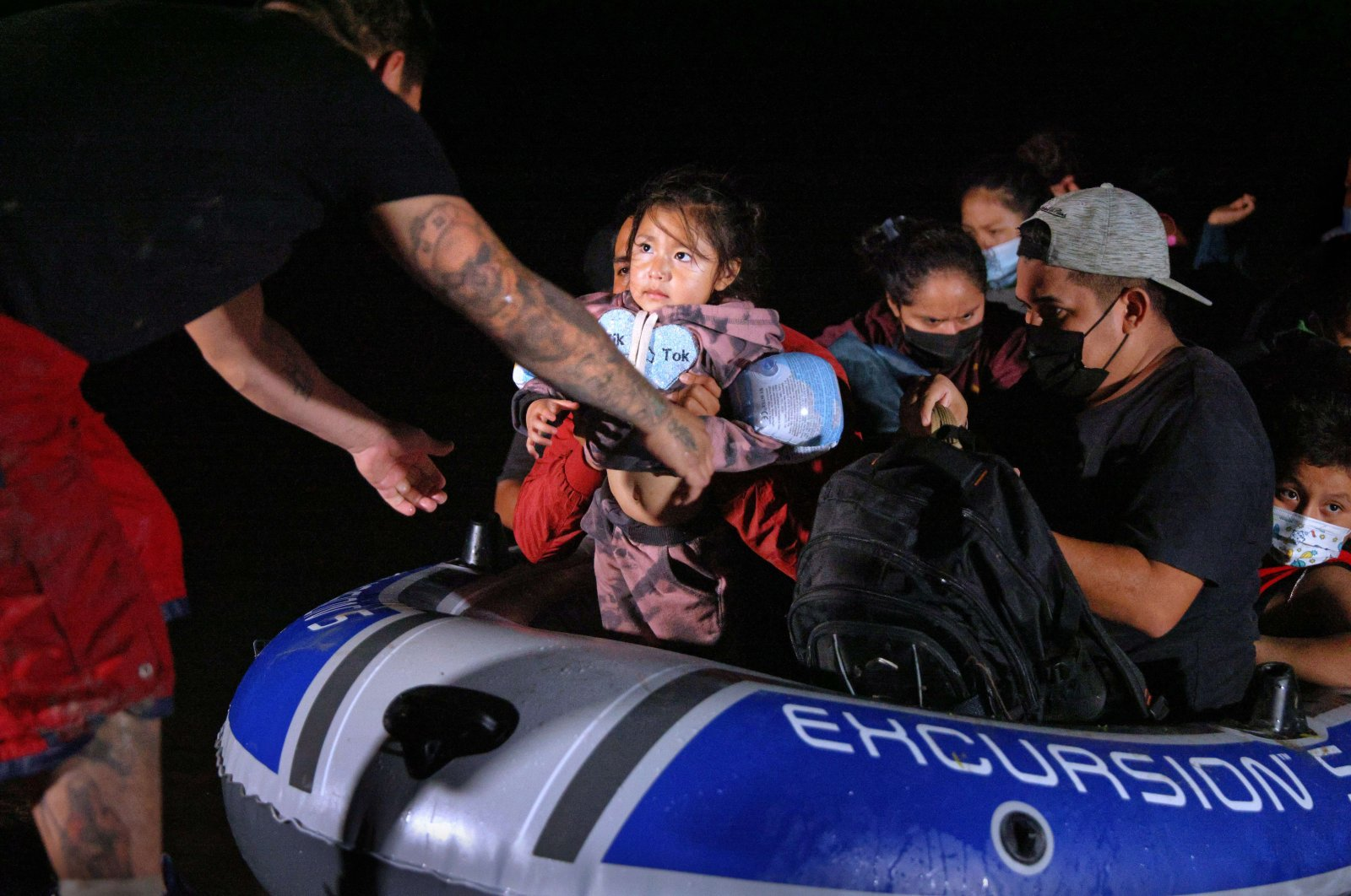 An immigrant child glances towards a human trafficker while being smuggled into the United States from Mexico in Roma, Texas, April 15, 2021. (AFP Photo)