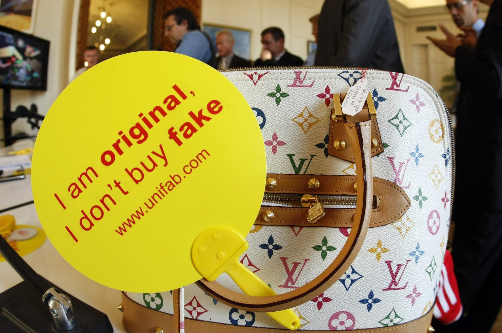A counterfeit Louis Vuitton luxury handbag is displayed by French customs officers before a destruction operation in Cannes, France, Sept. 28, 2009. (Reuters)