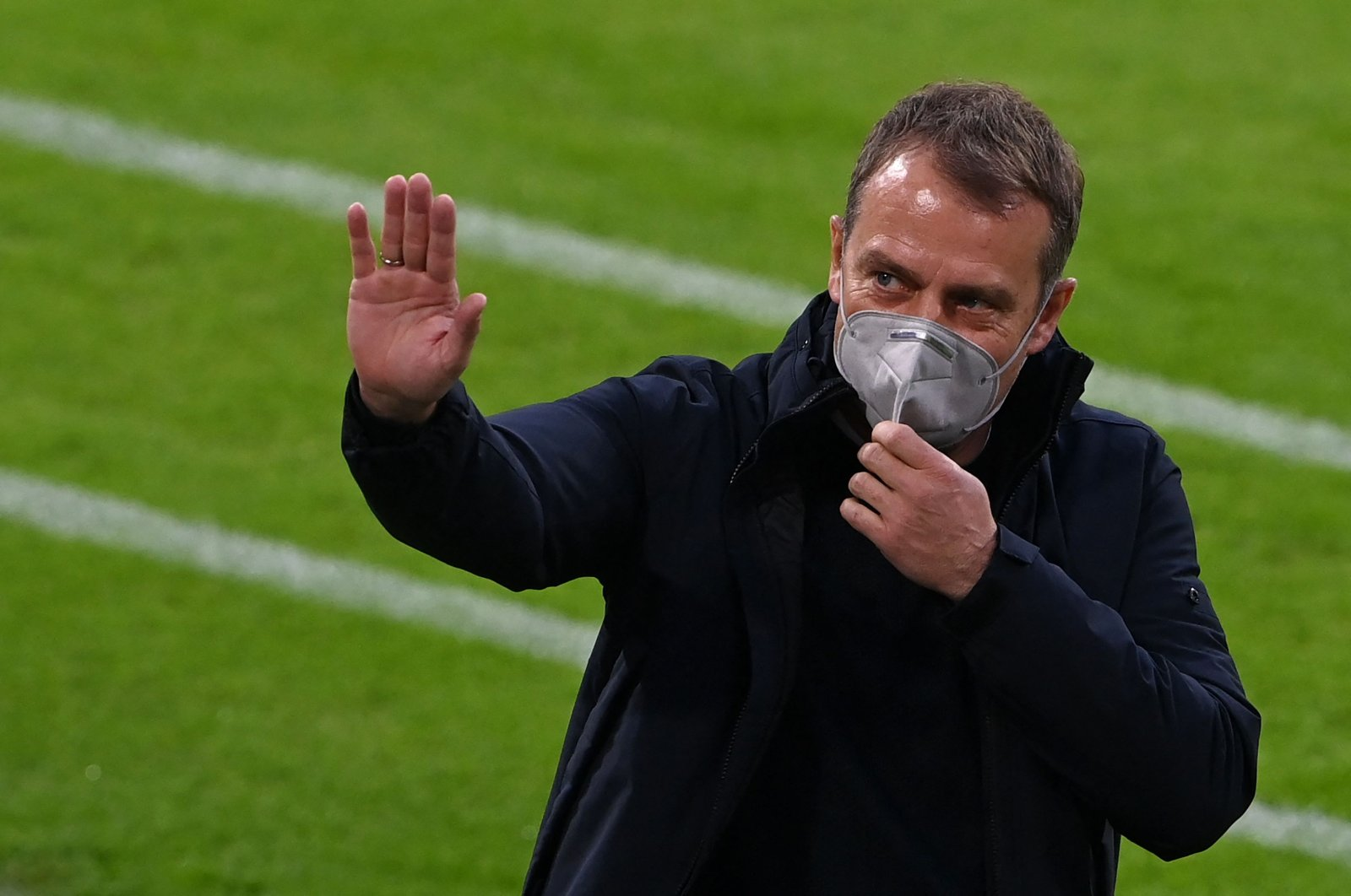 Bayern Munich's German head coach Hans-Dieter Flick waves as he arrives for an interview prior to the German first division Bundesliga football match in Munich, southern Germany, on April 20, 2021. (Photo by AFP)