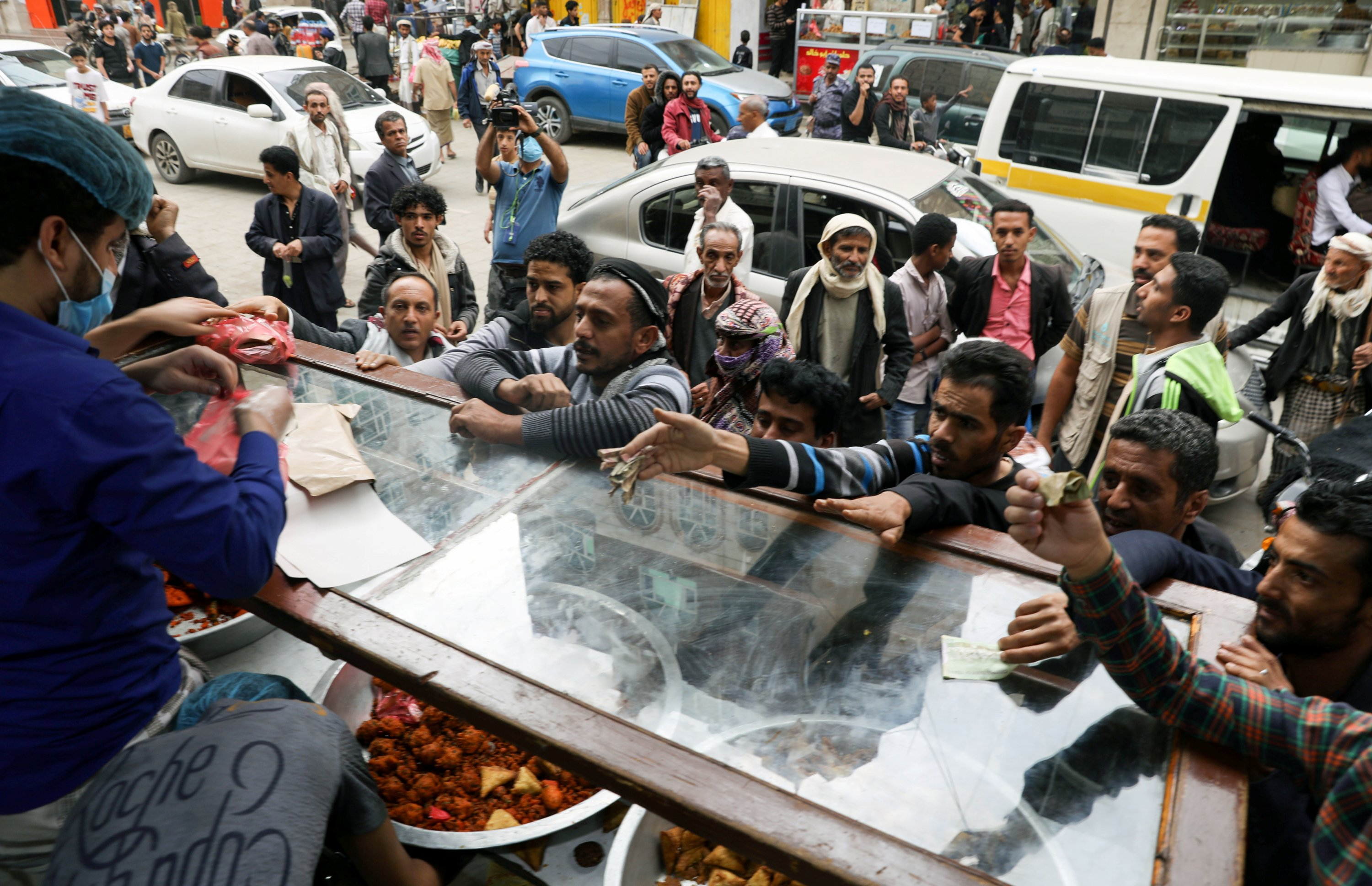 People gather outside a pastry shop to buy sambusa during the holy month of Ramadan in Sanaa, Yemen, April 15, 2021. (Reuters Photo)