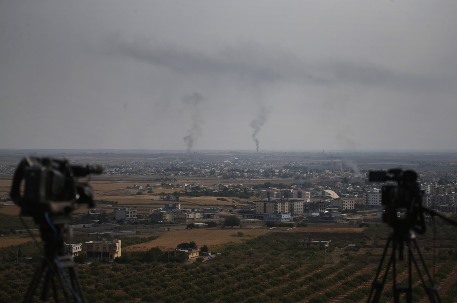 Television cameras are seen on a hilltop in Ceylanpınar, Şanlıurfa province, southeastern Turkey, as smoke billows from fires in the background in Ras al-Ain, Syria, Oct. 20, 2019. (AP File Photo)