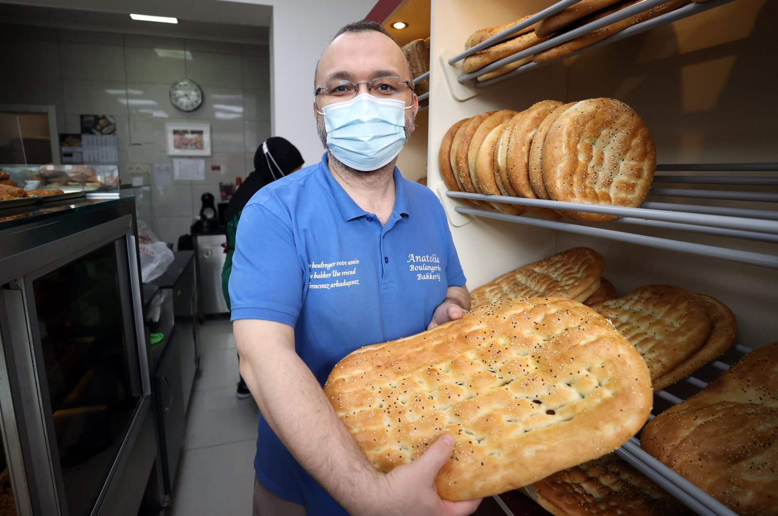 Turkish bakery owner Seçkin Dikmen shows off his bread at his shop in Brussels, Belgium, April 21, 2021. (AA Photo)