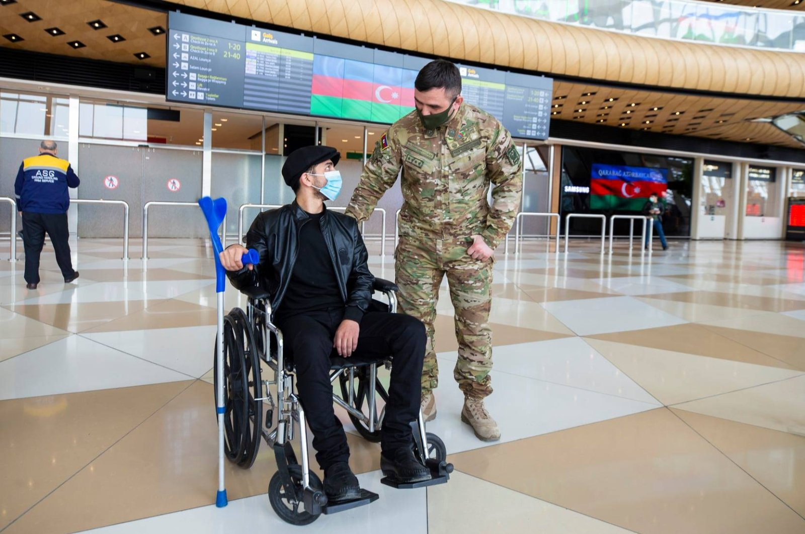 A soldier stands next to a man in a wheelchair, Baku, Azerbaijan, April 21, 2021. (AA Photo)  Azerbaijan sent 12 wounded soldiers to Turkey for treatment.