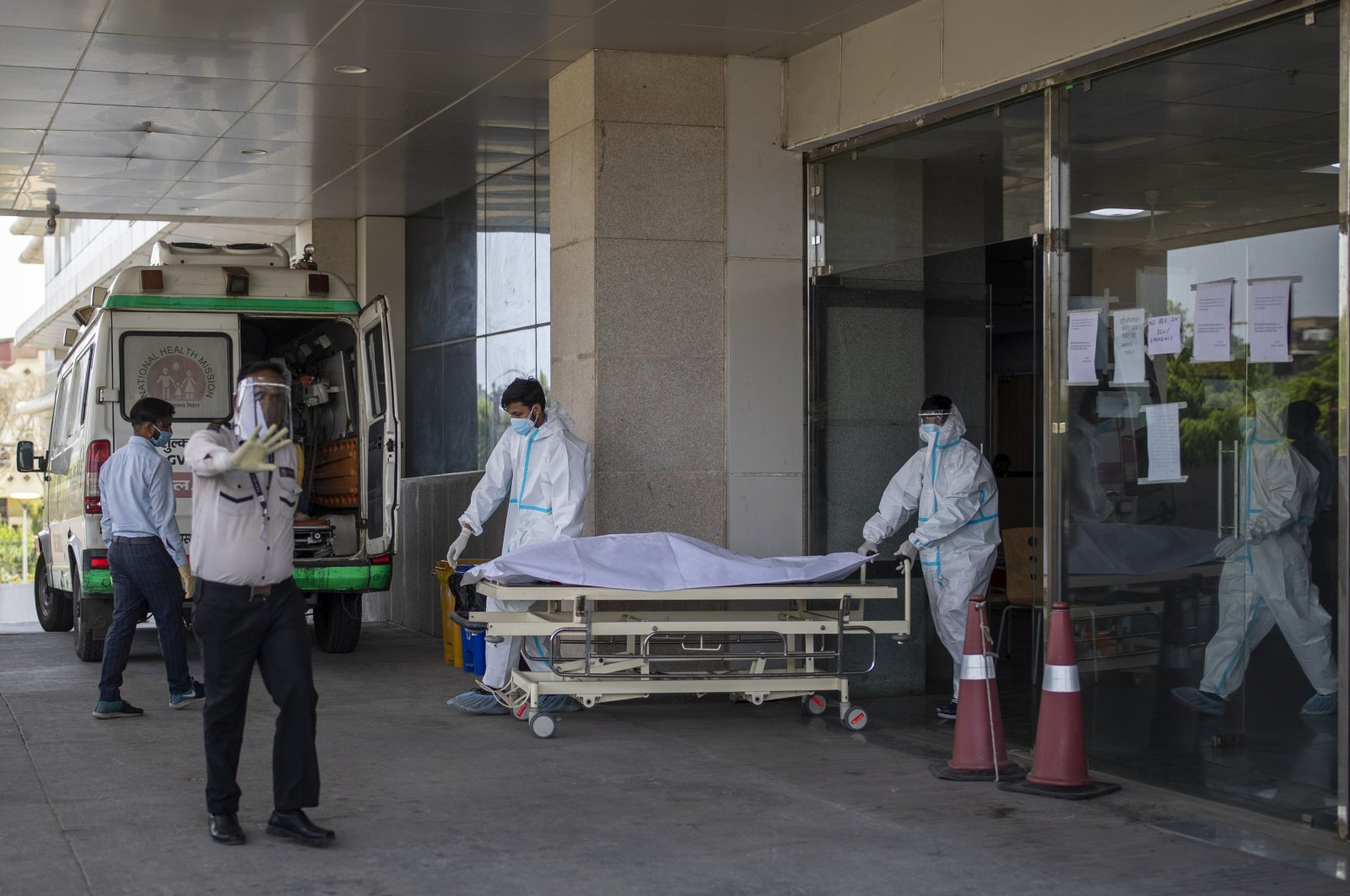 A security guard objects to taking pictures as hospital staff shift the body of a COVID-19 patient on a stretcher to a waiting ambulance at a government COVID-19 hospital in Noida, a suburb of New Delhi, India, April 21, 2021. (AP Photo)