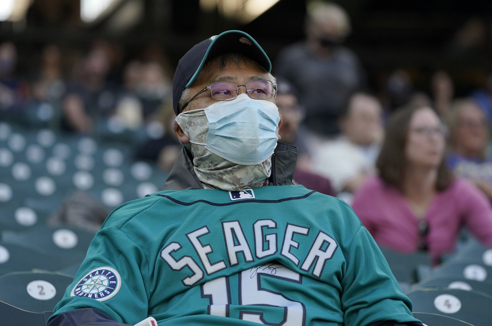 A fan wears two masks and a backward Kyle Seager jersey as he watches a baseball game between the Mariners and the Houston Astros, in Seattle, Washington, April 17, 2021. (AP Photo)