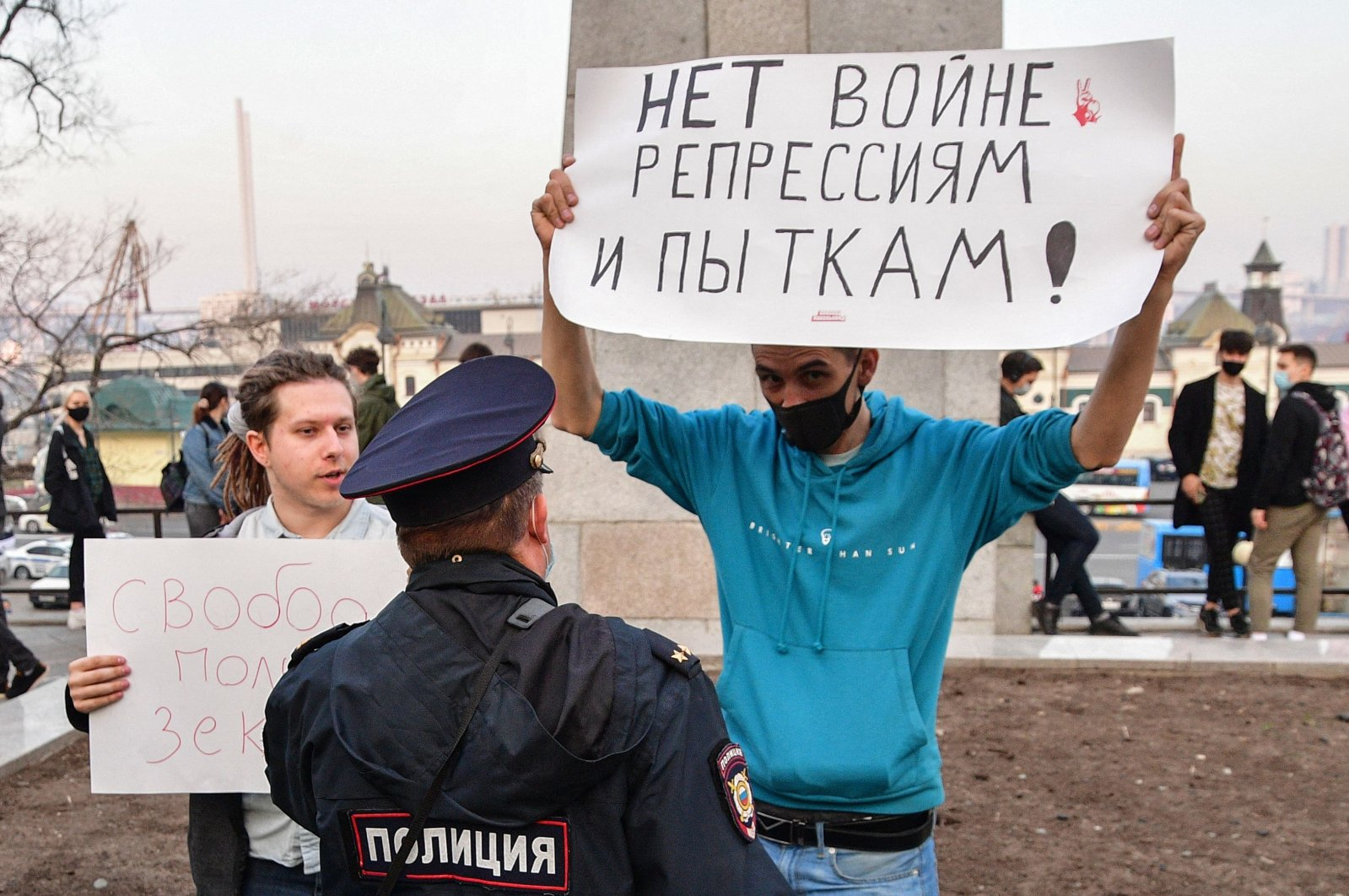 """A Russian police officer speaks with an opposition supporter holding a poster reading """"No war, repressions and tortures!"""" during a rally in support of jailed Kremlin critic Alexei Navalny in Vladivostok, Russia, April 21, 2021. (AFP Photo)"""