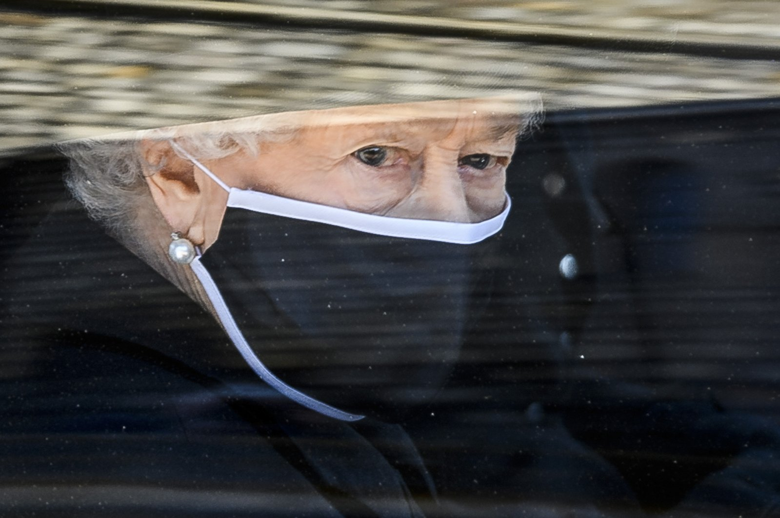 Britain's Queen Elizabeth II follows the coffin in a car as it makes it's way past the Round Tower during the funeral of Britain's Prince Philip inside Windsor Castle in Windsor, England, April 17, 2021. (AP Photo)