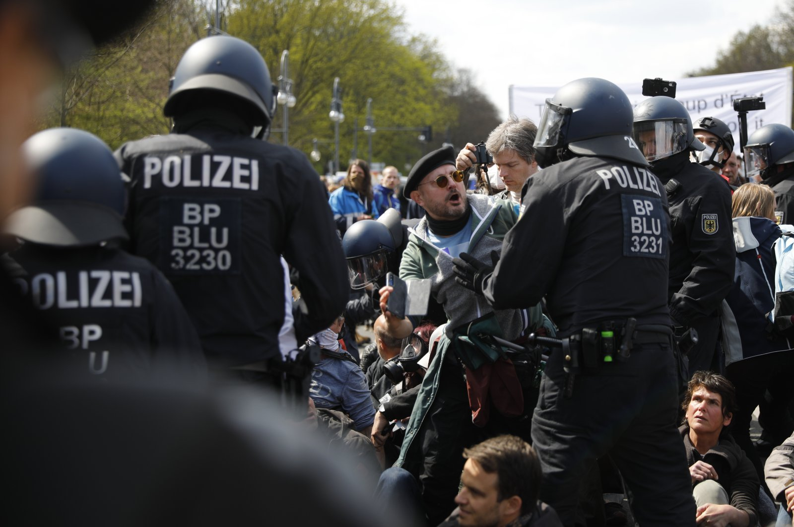 Police officers argue with demonstrators after police stop a protest rally against the German government's policy to battle the coronavirus pandemic in Berlin, Germany, April 21, 2021. (AP Photo)