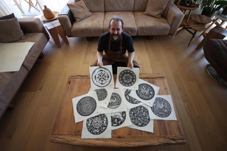 Cumhur Aygün holds a couple of 1,000-year-oldmotifs he printed on handmade paper, Bursa, Turkey, April 21, 2021. (AA Photo)