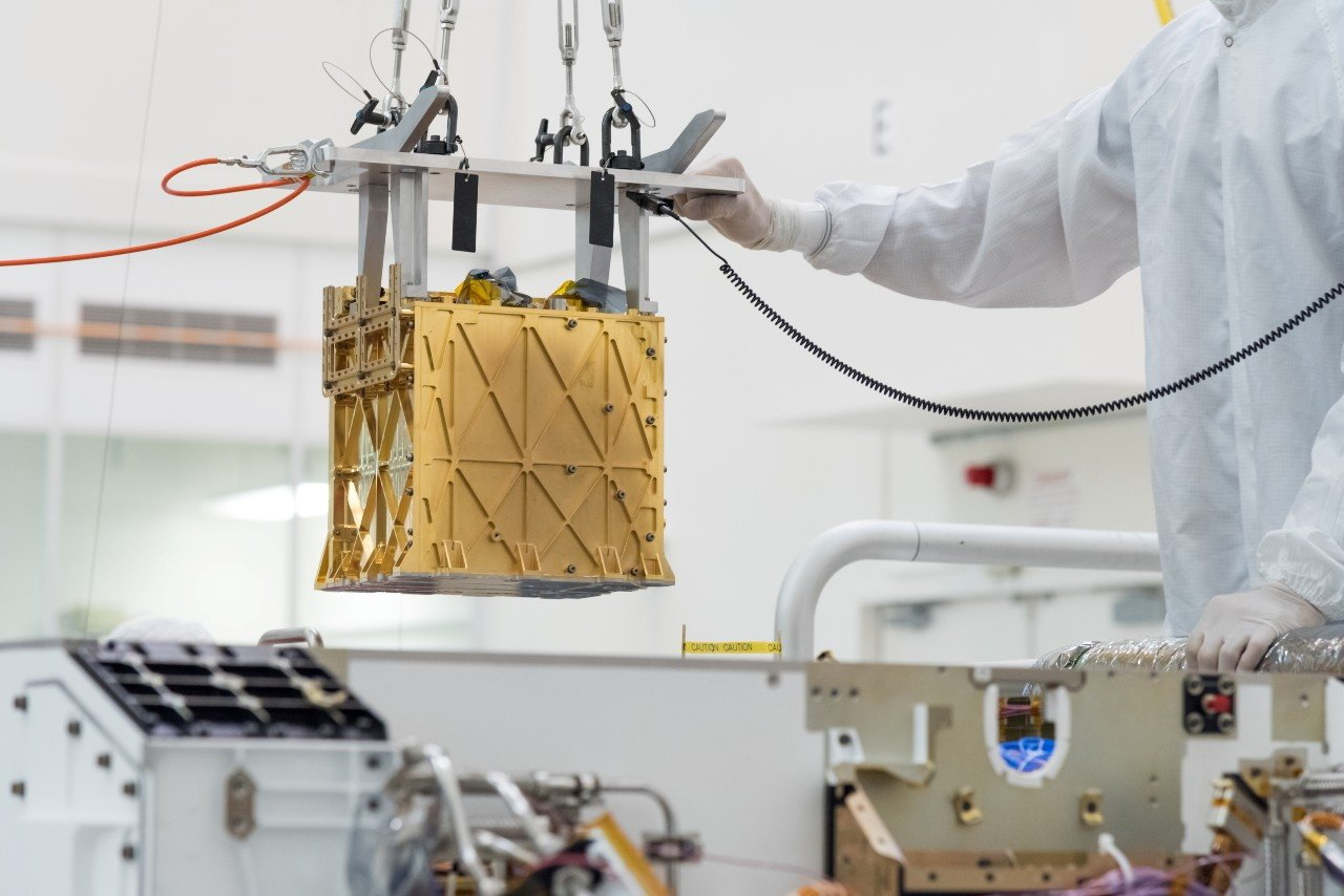 Technicians at NASA's Jet Propulsion Laboratory lower the Mars Oxygen In-Situ Resource Utilization Experiment (MOXIE) instrument into the belly of the Perseverance rover in an undated photograph in Pasadena, California, U.S. (NASA Handout via Reuters)