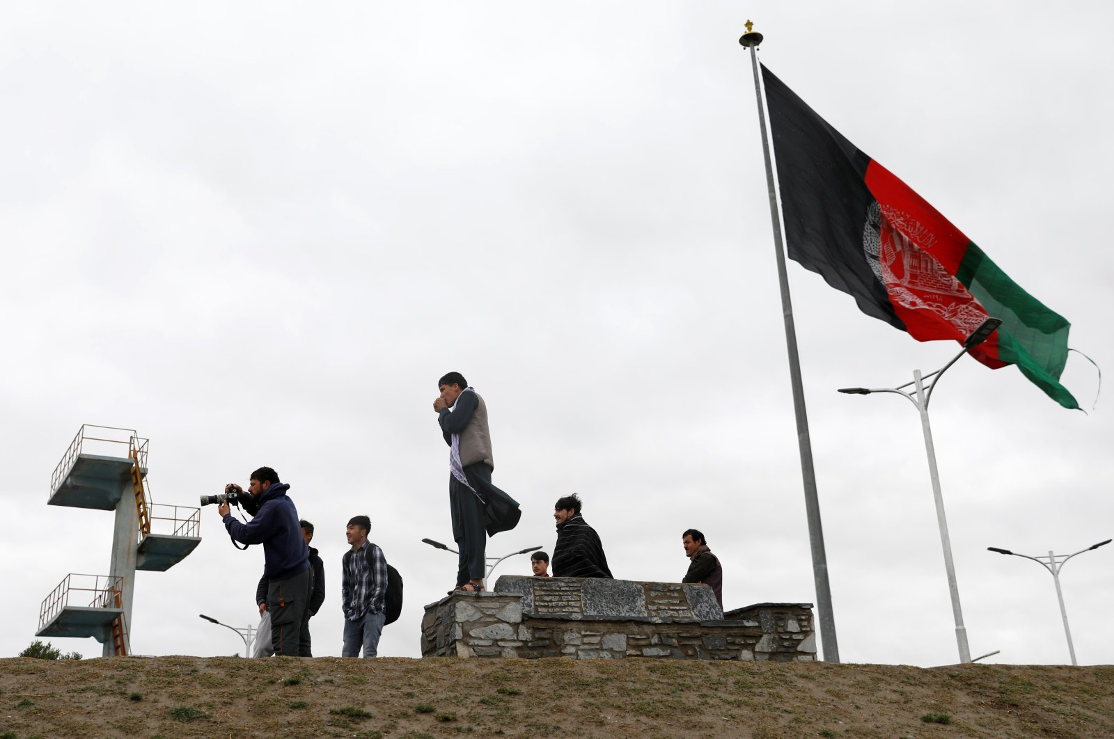 Youths take pictures next to an Afghan flag on a hilltop overlooking Kabul, Afghanistan, April 15, 2021. (REUTERS Photo)