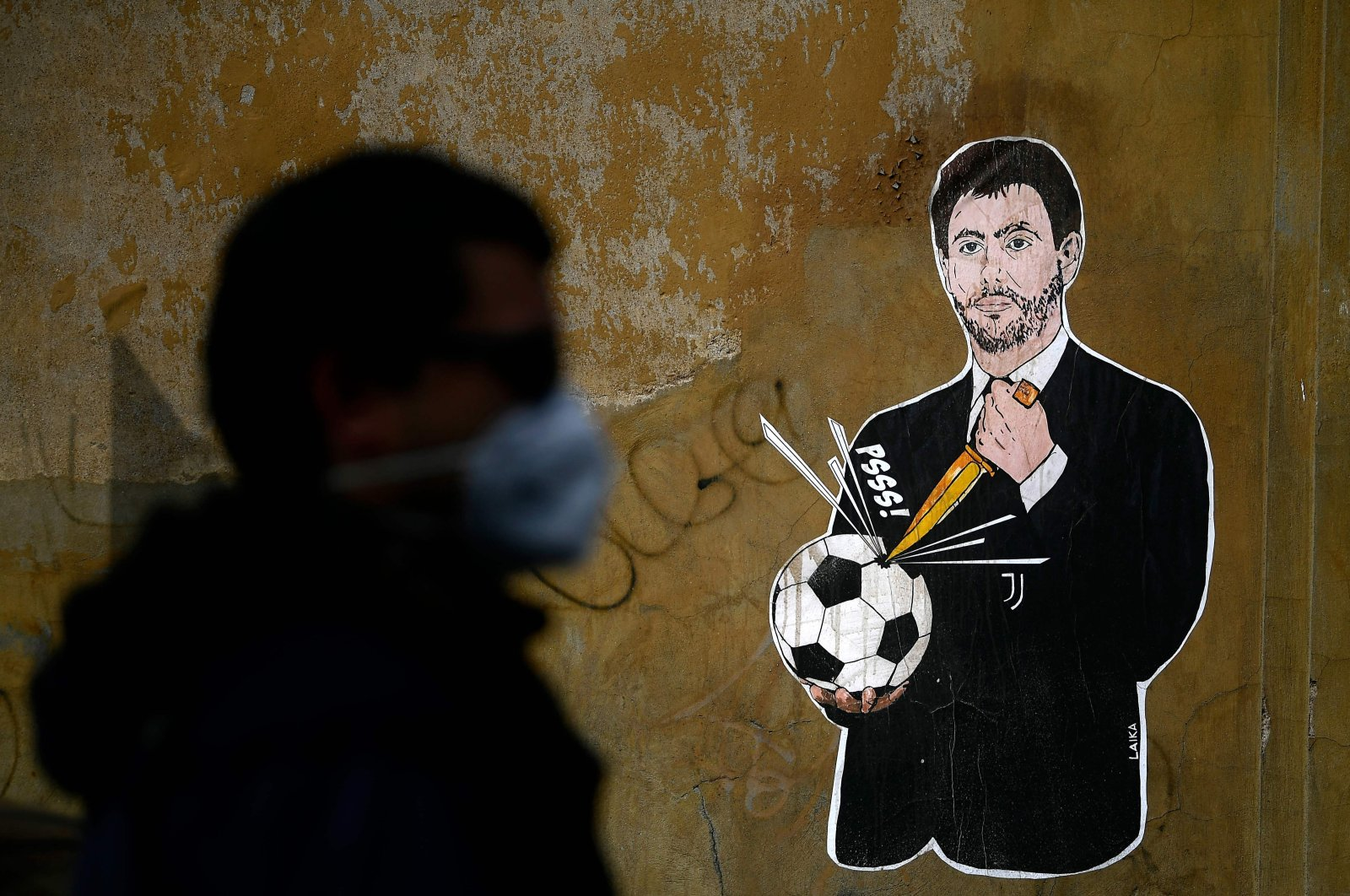 """A man walks past a graffiti entitled """"The failed coup"""" (Il Golpe Fallito) by Italian artist Laika, showing Juventus President Andrea Agnelli puncturing a football, near the headquarters of the Italian Football Federation, Rome, Italy, April 21, 2021."""