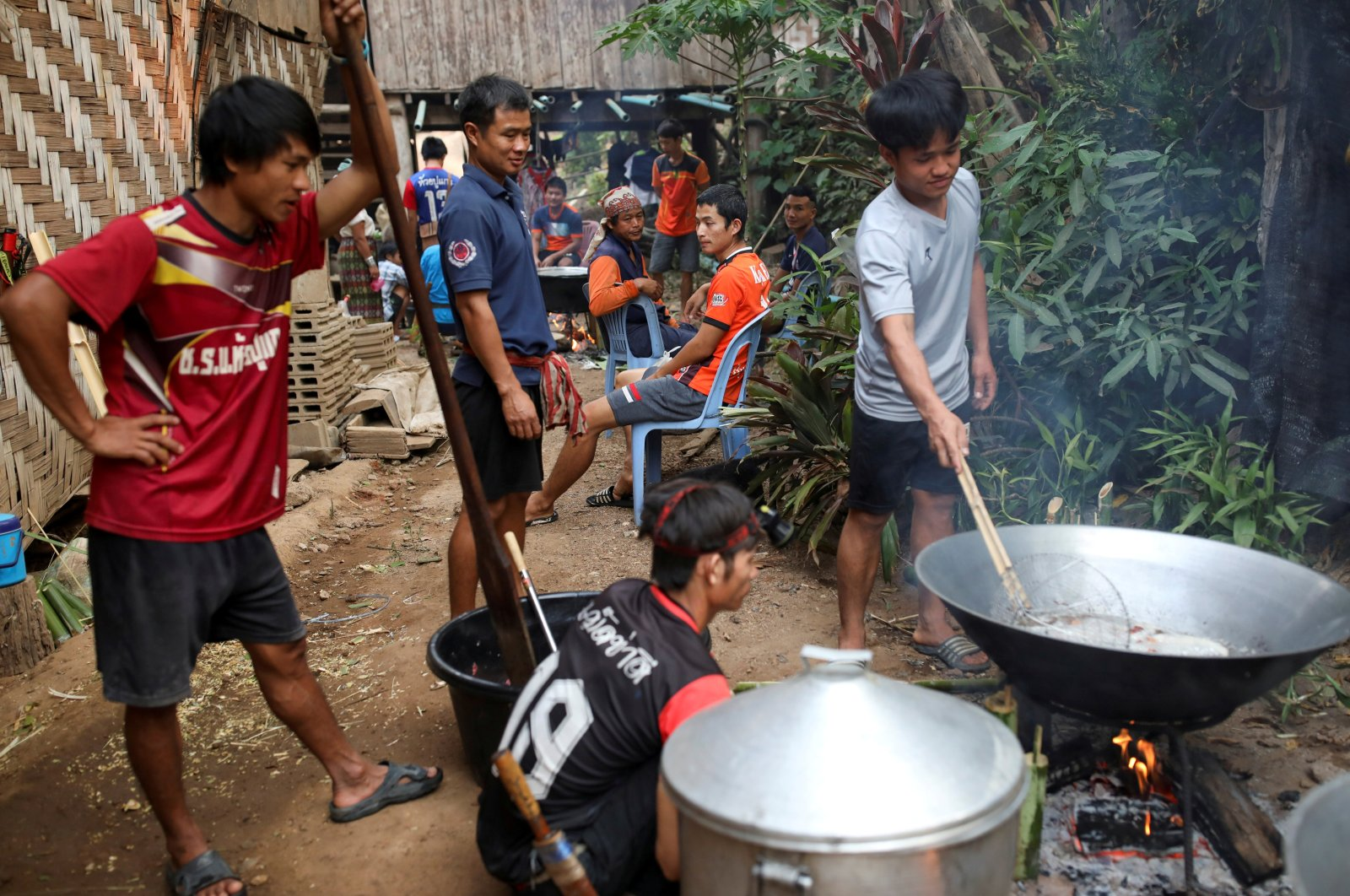 Men prepare food during a death anniversary in the Kayan village, where people who fled from Myanmar during the 1990s war between Myanmar's army and ethnic army groups, live, Mae Hong Son, Thailand, March 25, 2021. (Reuters Photo)