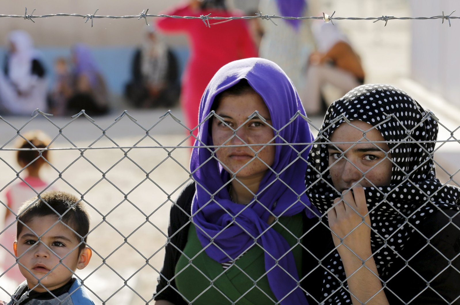 Yazidi refugees stand behind fences at a Syrian and Iraqi refugee camp in the town of Midyat in Mardin province, southeastern Turkey, June 20, 2015. (Reuters Photo)