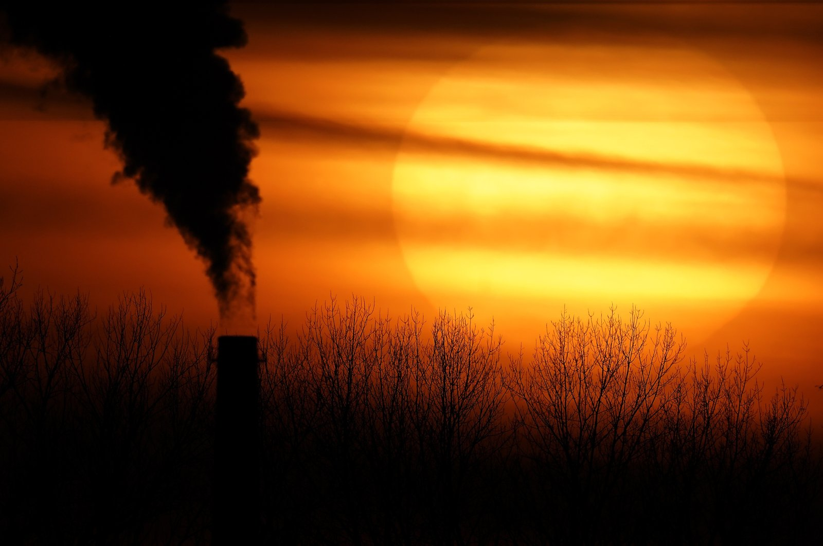 Emissions from a coal-fired power plant are silhouetted against the setting sun in Independence, Mo., U.S., Feb. 1, 2021. (AP File Photo)