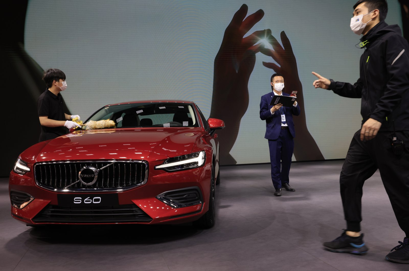 A worker cleans a Volvo S60 during the Shanghai Auto Show, Shanghai, China, Wednesday, April 21, 2021. (AP Photo)