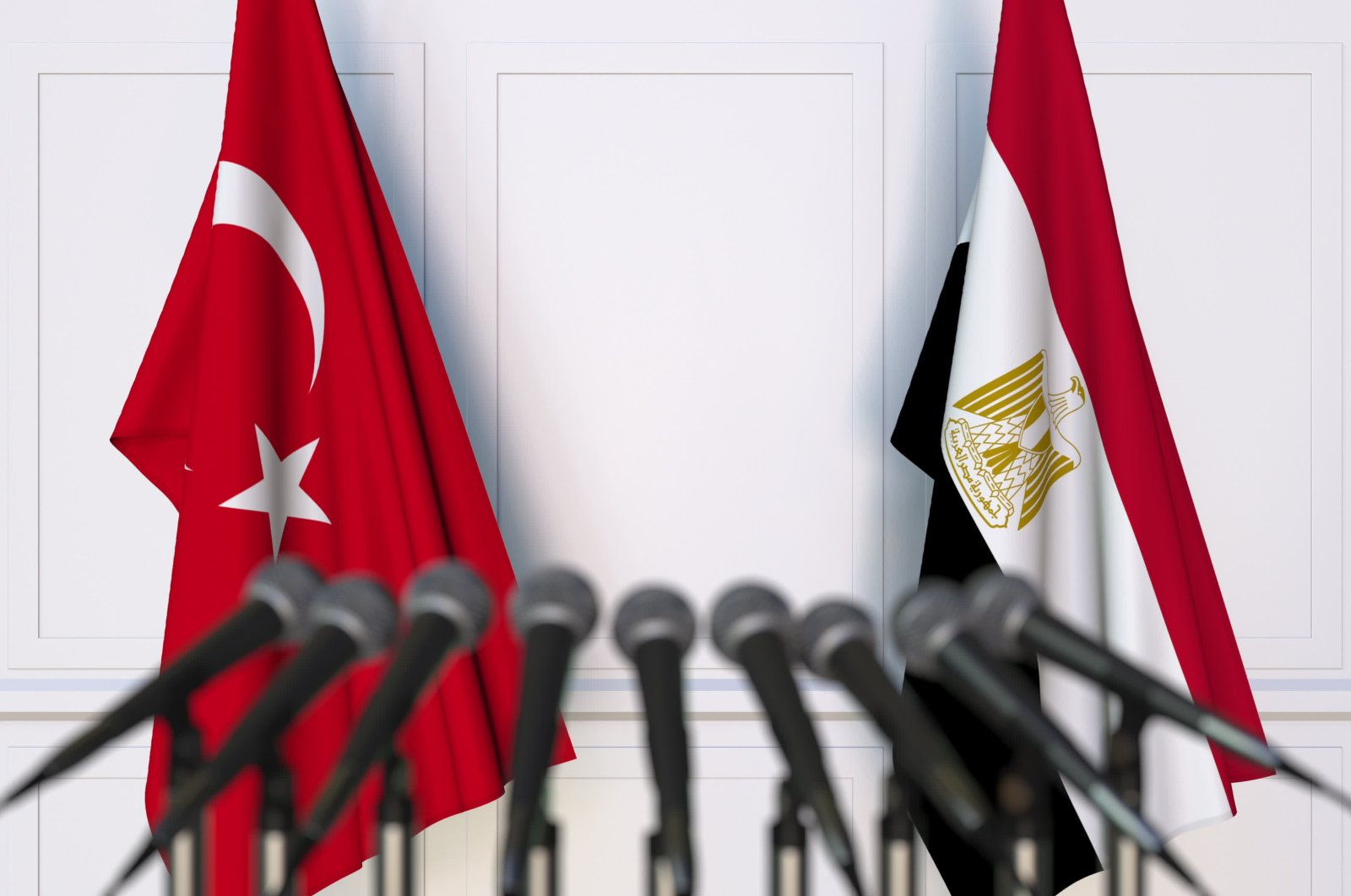 The flags of Turkey and Egypt are seen in front of microphones in this photo. (Photo by Shutterstock)