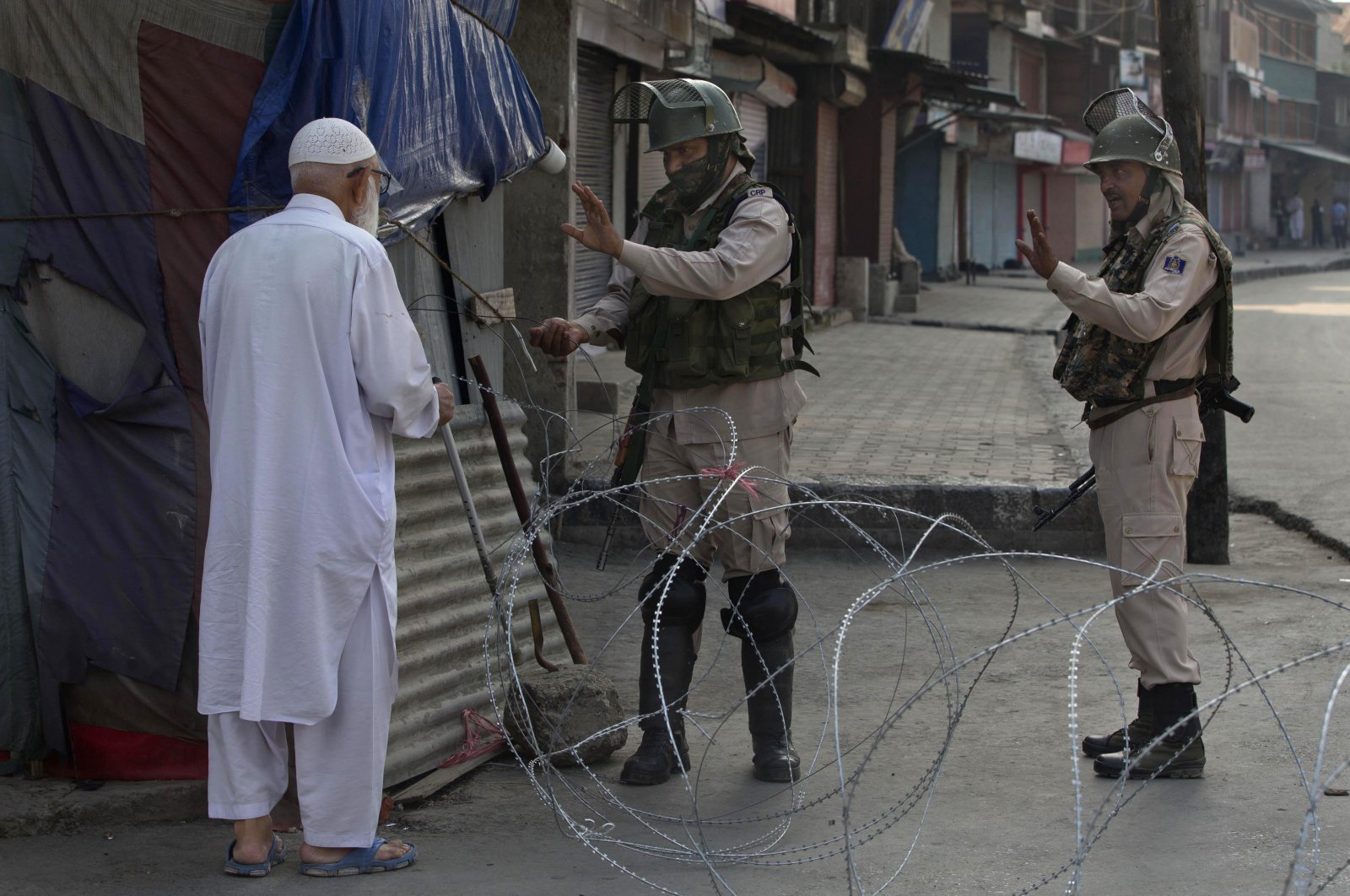 An elderly Kashmiri man is stopped before being allowed to pass near a temporary checkpoint set up by Indian paramilitary soldiers during lockdown in Srinagar, Indian controlled Kashmir, Friday, Aug. 23, 2019. (AP Photo)
